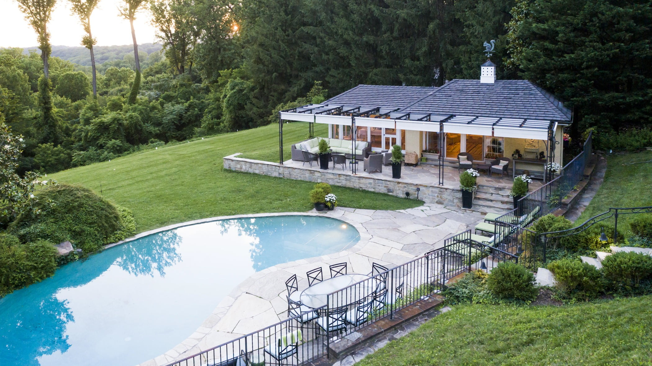 Luxury pool house custom designed for a home remodel with a large seating space and large metal pergola (House side view) (3)