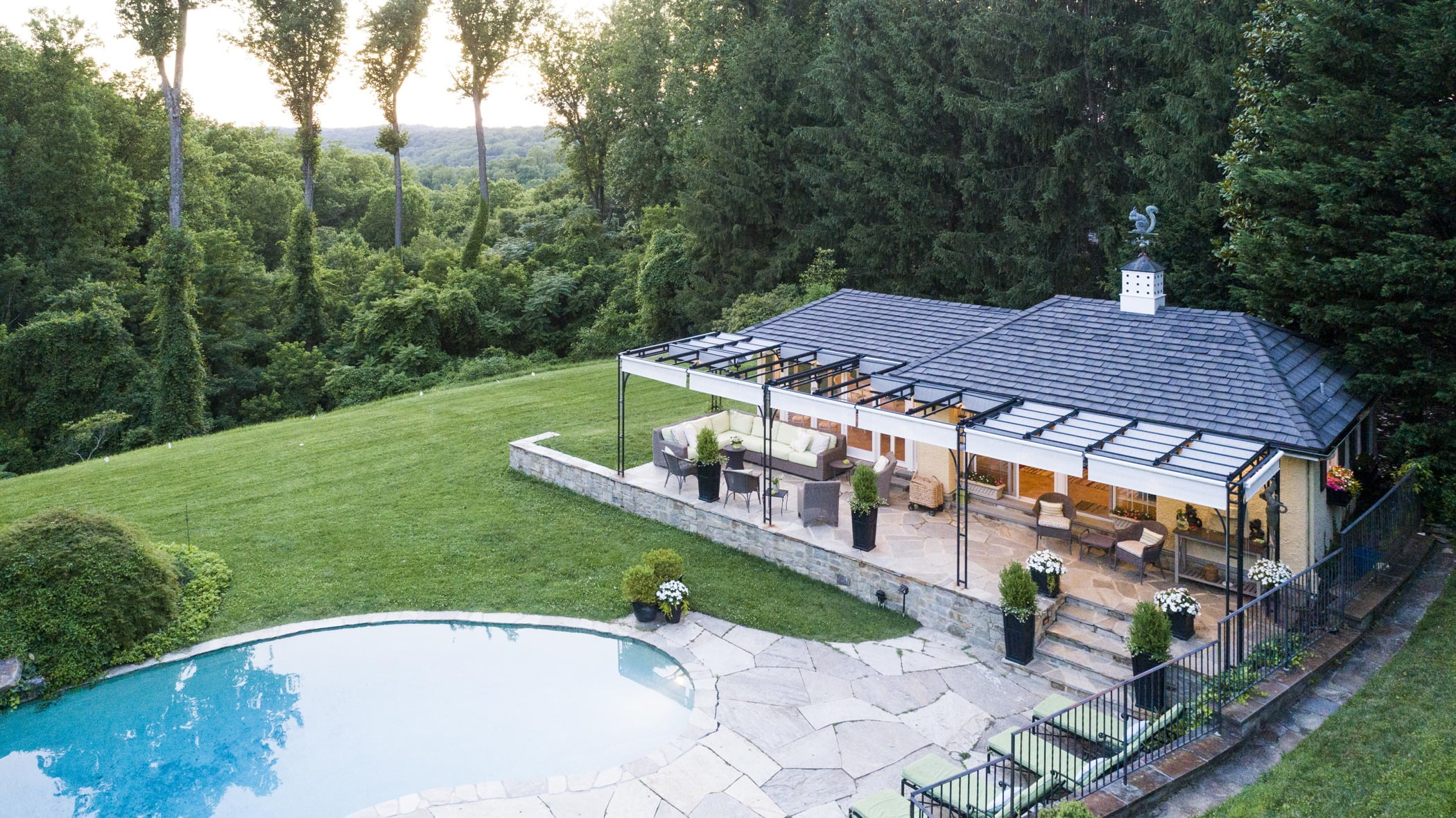 Luxury pool house custom designed for a home remodel with a large seating space and large metal pergola (Aerial view)