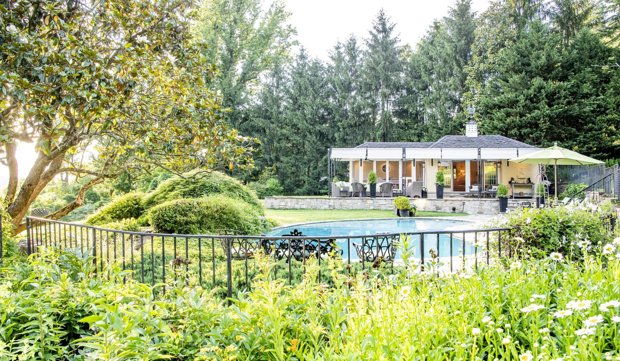 Luxury pool house custom designed for a home remodel with a large seating space and large metal pergola (Outside fence view)