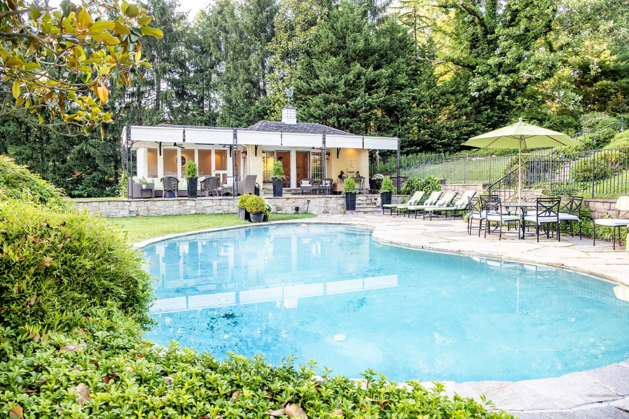 Luxury pool house custom designed for a home remodel with a large seating space and large metal pergola (Full pool view)