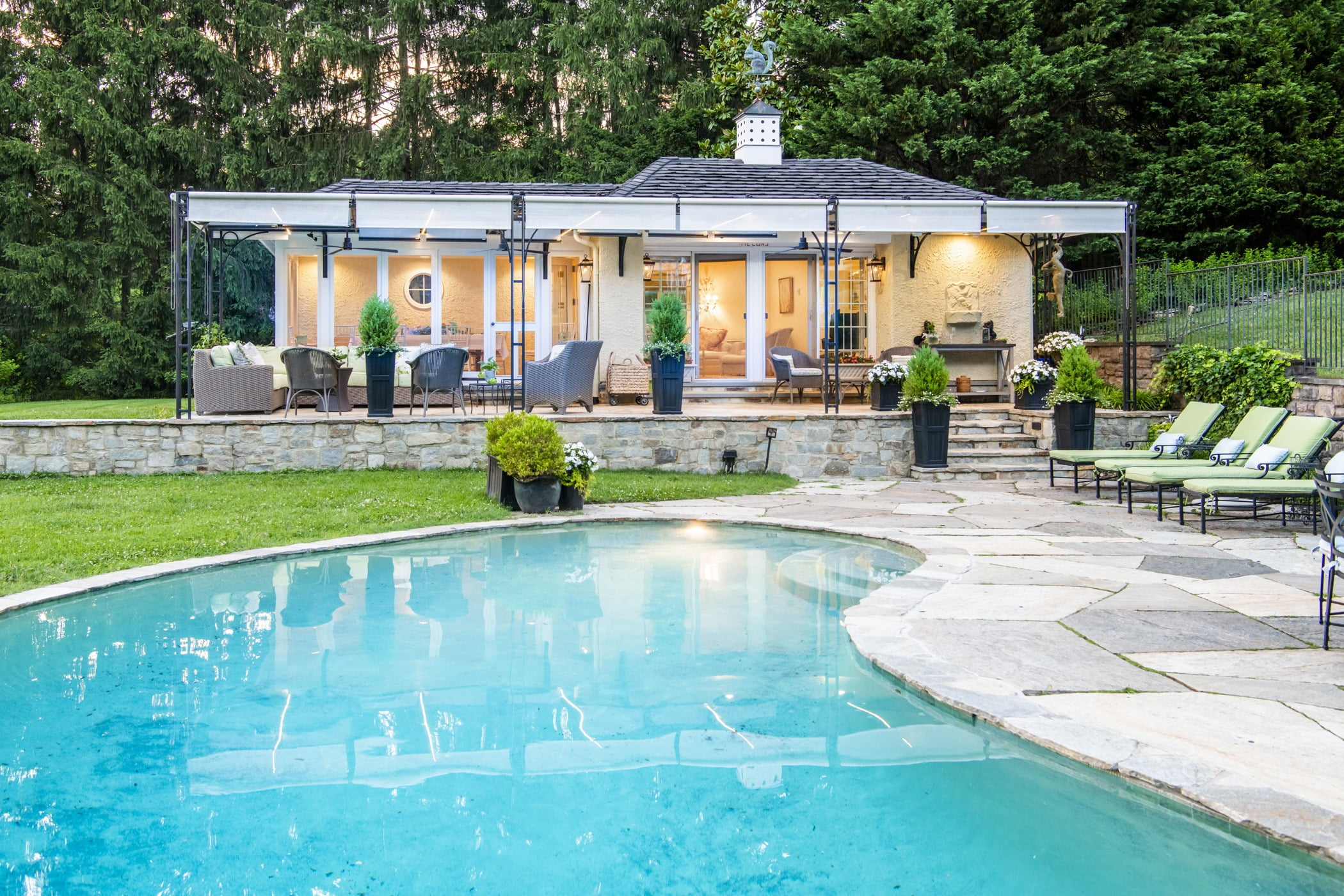Luxury pool house custom designed for a home remodel with a large seating space and large metal pergola (Pool view)