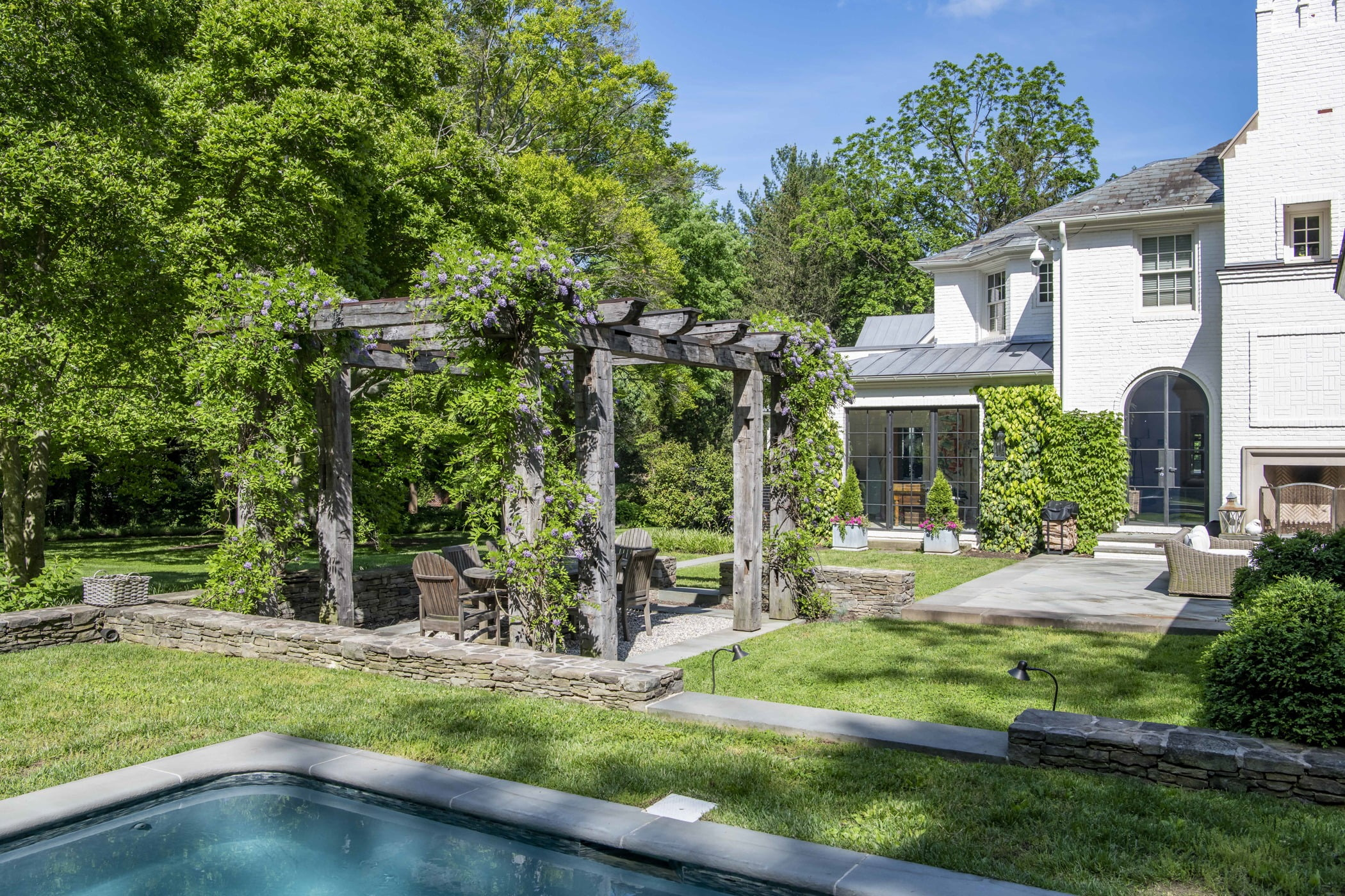 Ivy-covered wooden pergola, outdoor seating and dining area, and rest of backyard