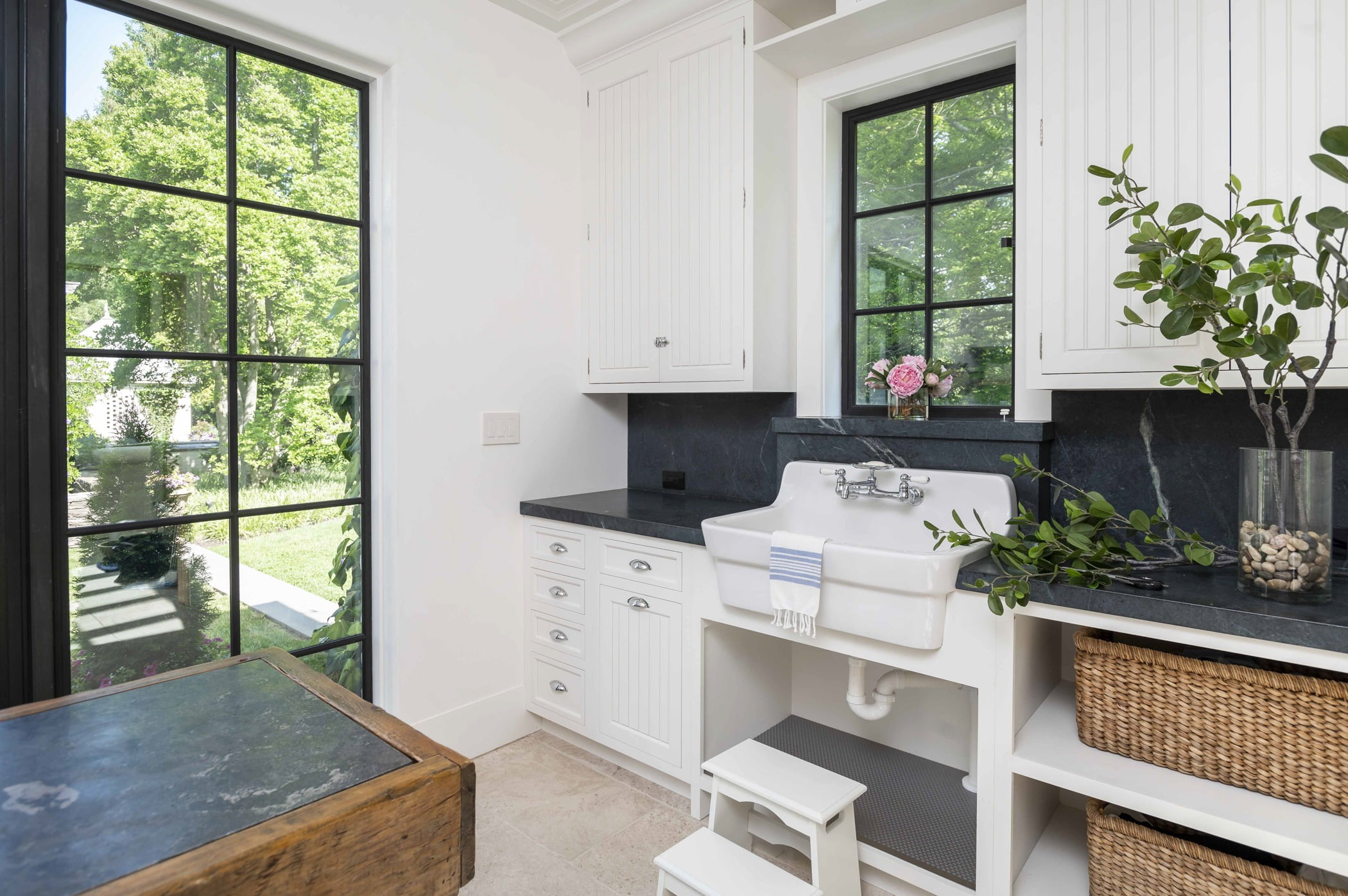 Coastal style washroom with white paneled cabinetry, dark granite countertops, and a dark metal window and door accent (Different angle)