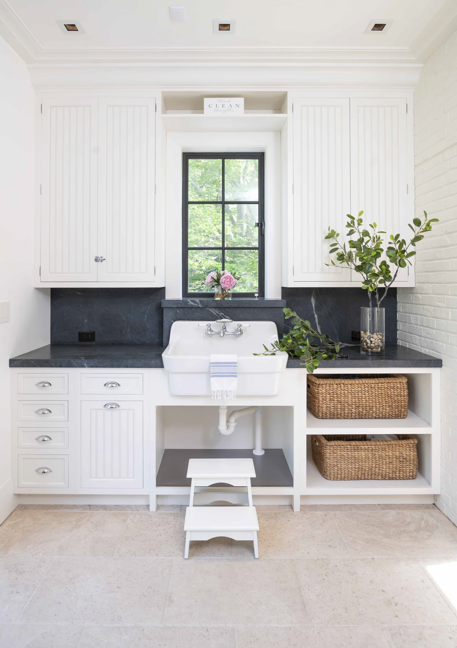 Coastal style washroom with white paneled cabinetry, dark granite countertops, and a dark metal window and door accent