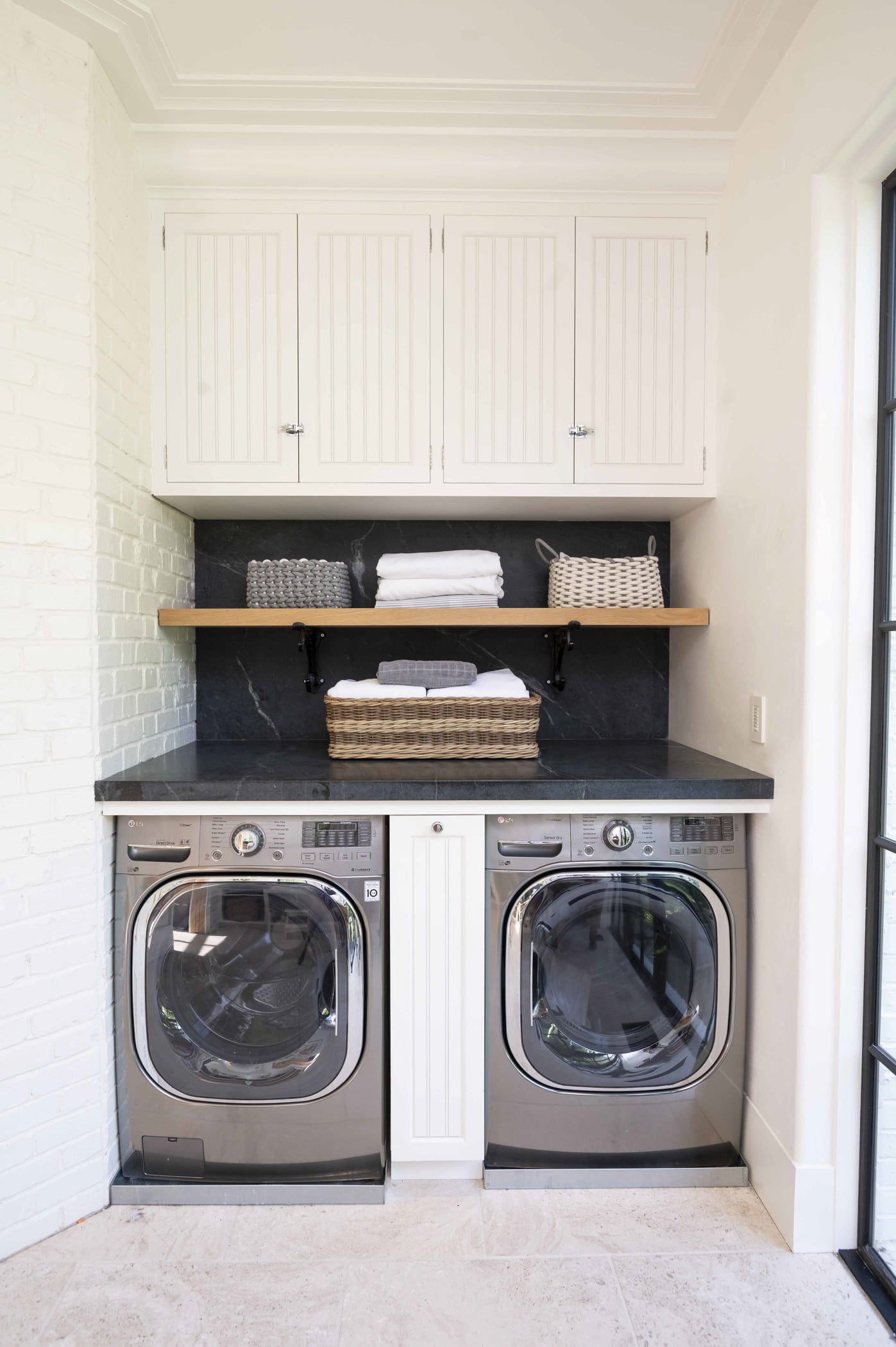 Coastal laundry room with white paneled cabinetry, dark granite countertops, and wooden shelving