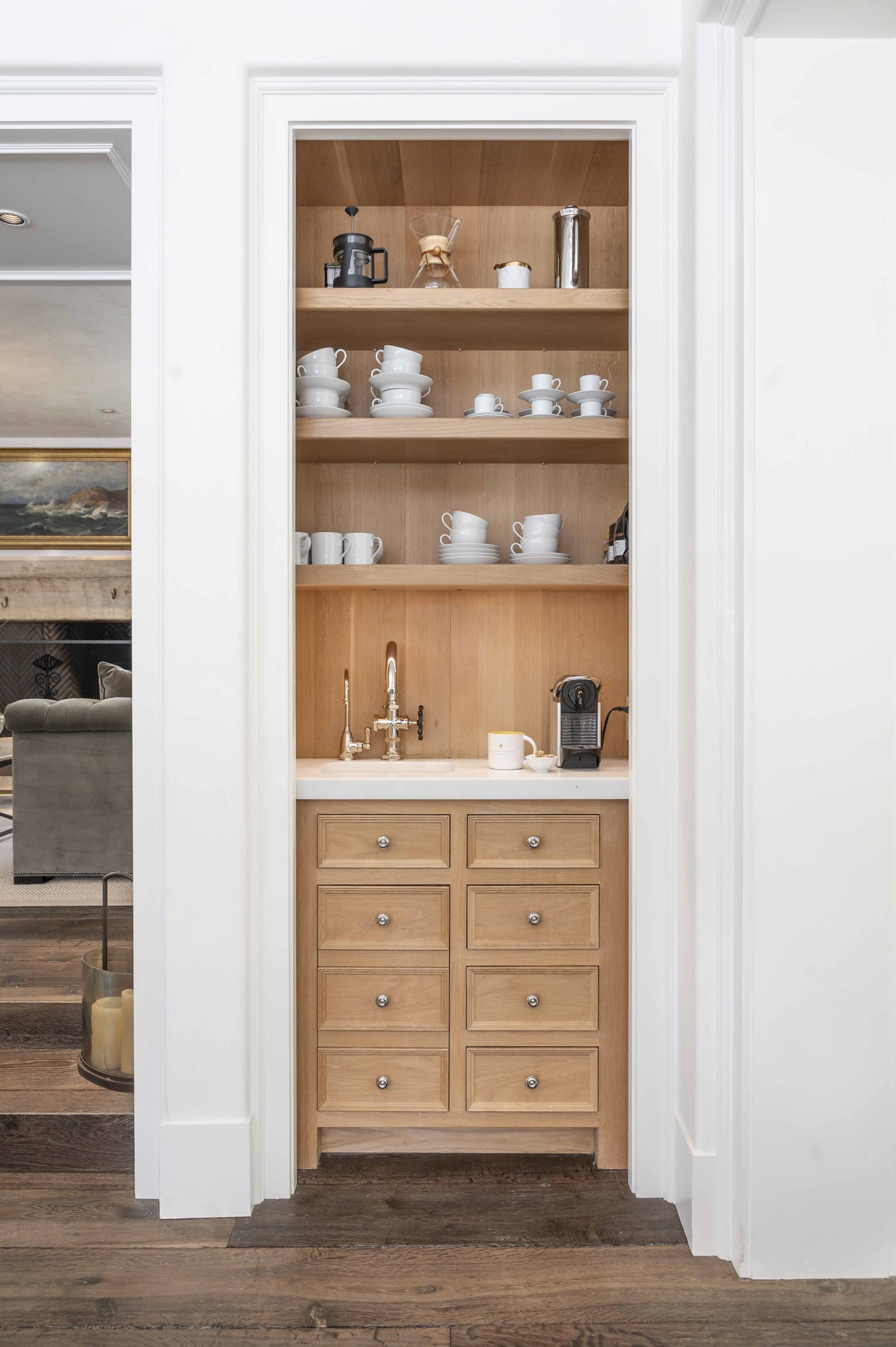 Transitional shelving space with light wood cabinetry and white marble countertops
