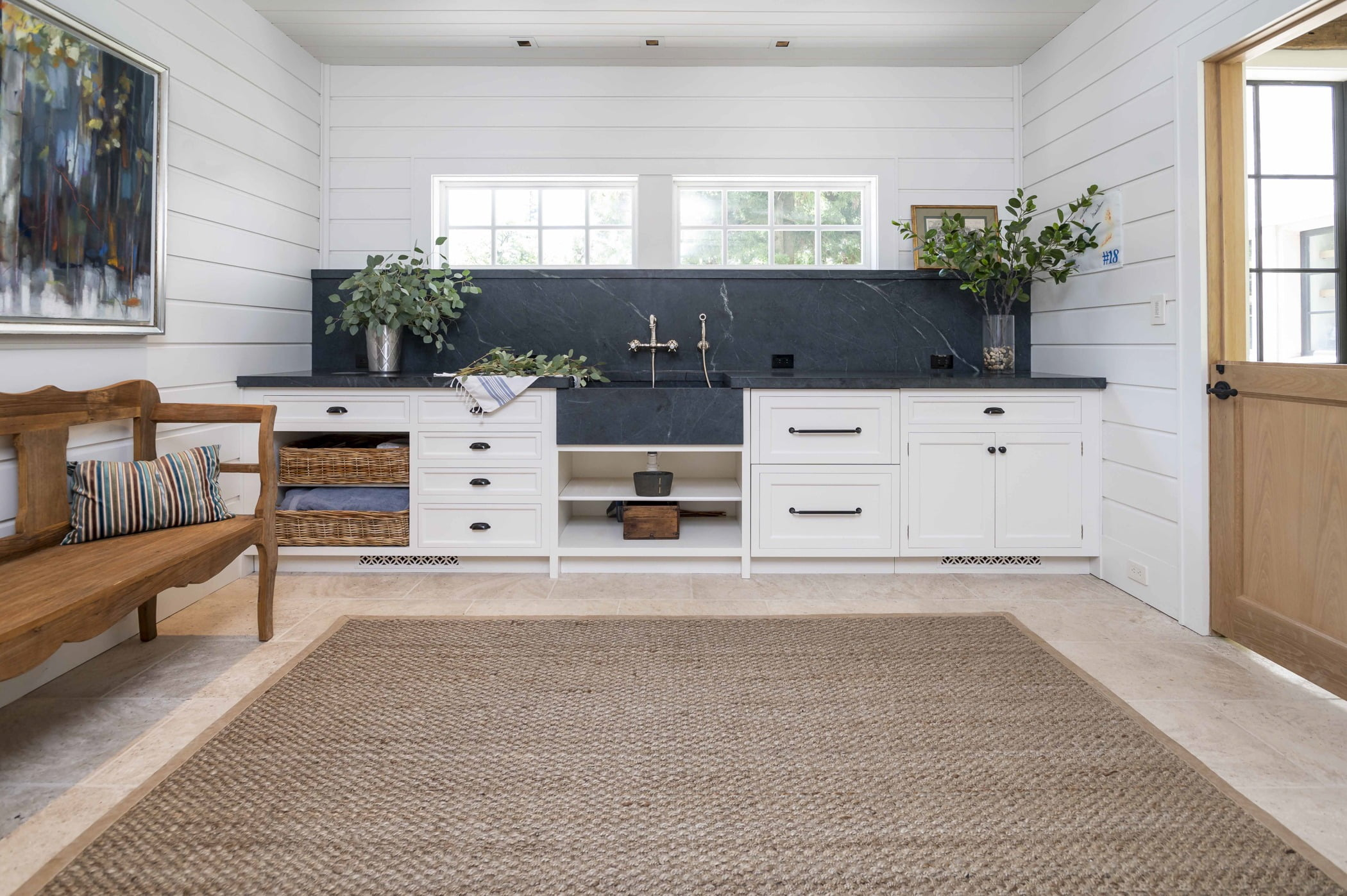 Transitional sink/washroom space with white cabinetry, grey-blue countertops, and white paneling on walls and ceiling