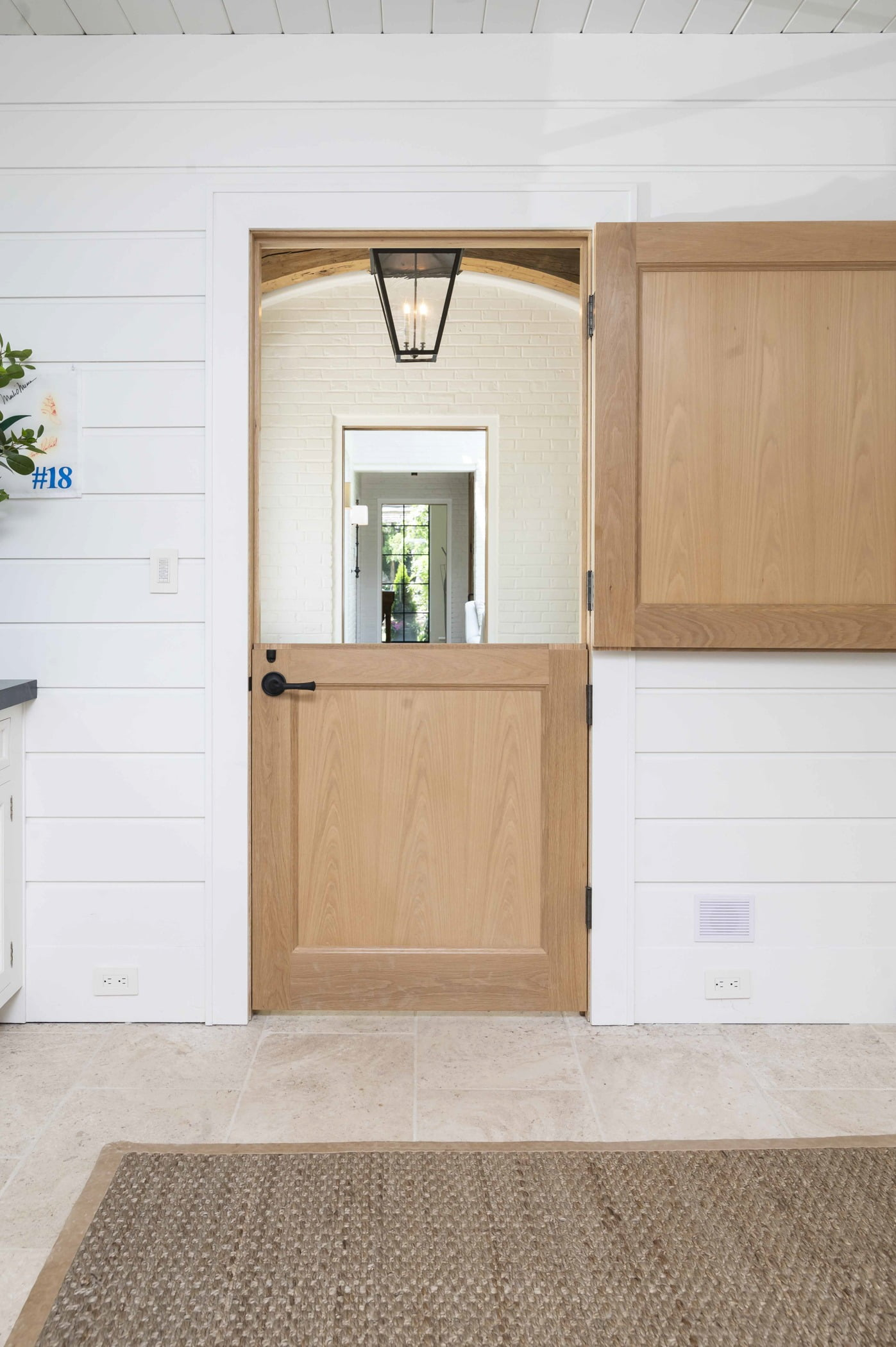 Transitional light hardwood interior dutch door with white panel walls and ceiling