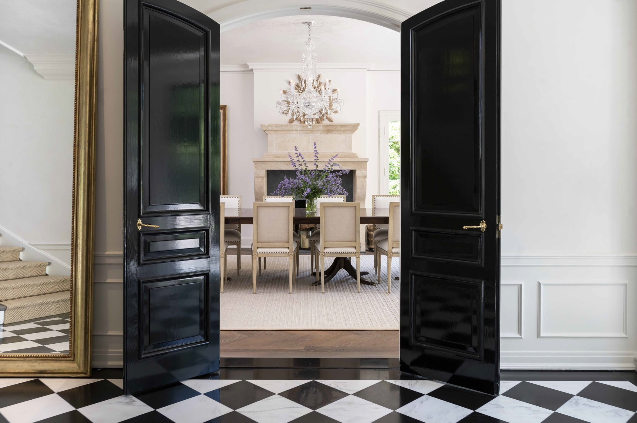 Traditional dining room through double arched black doors with black and white checkered tile flooring