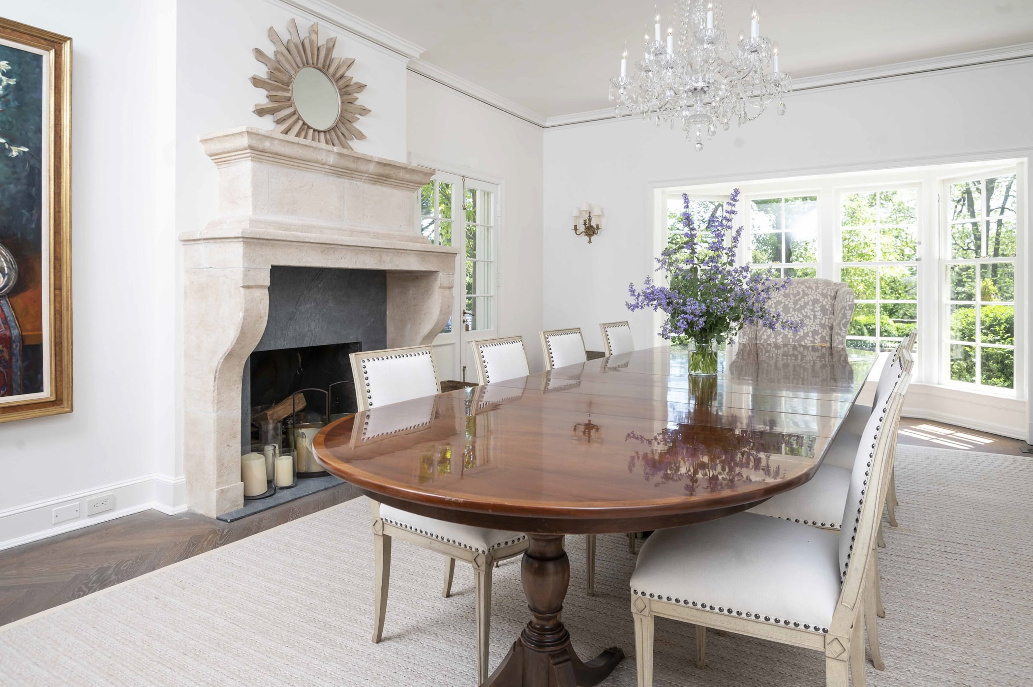 Traditional dining room with decorative stone fireplace, wood table, crystal chandelier and decorative cream color chairs