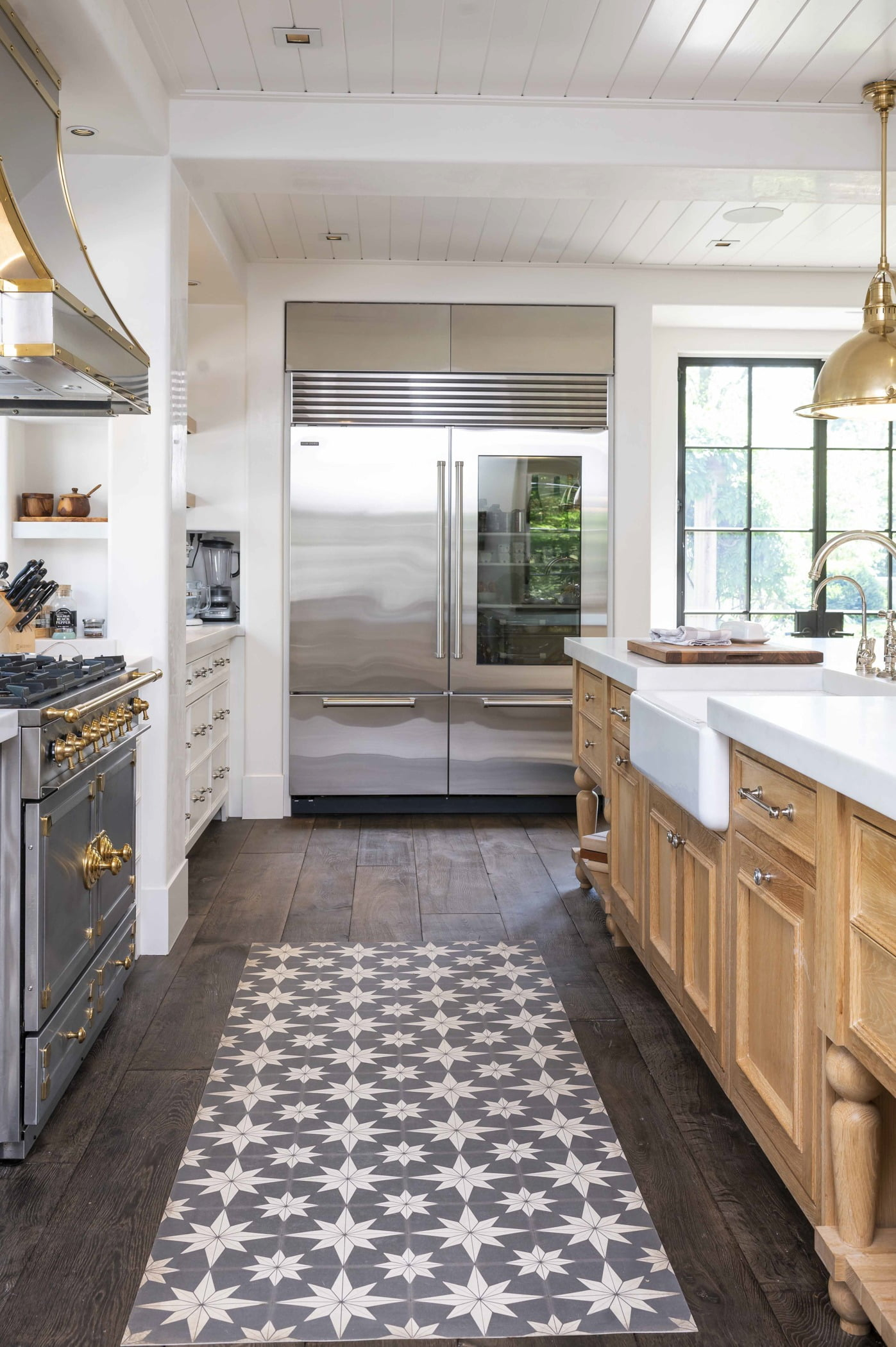 Transitional kitchen with light wood cabinetry and white marble countertops, stainless steel appliances, and dark hardwood flooring