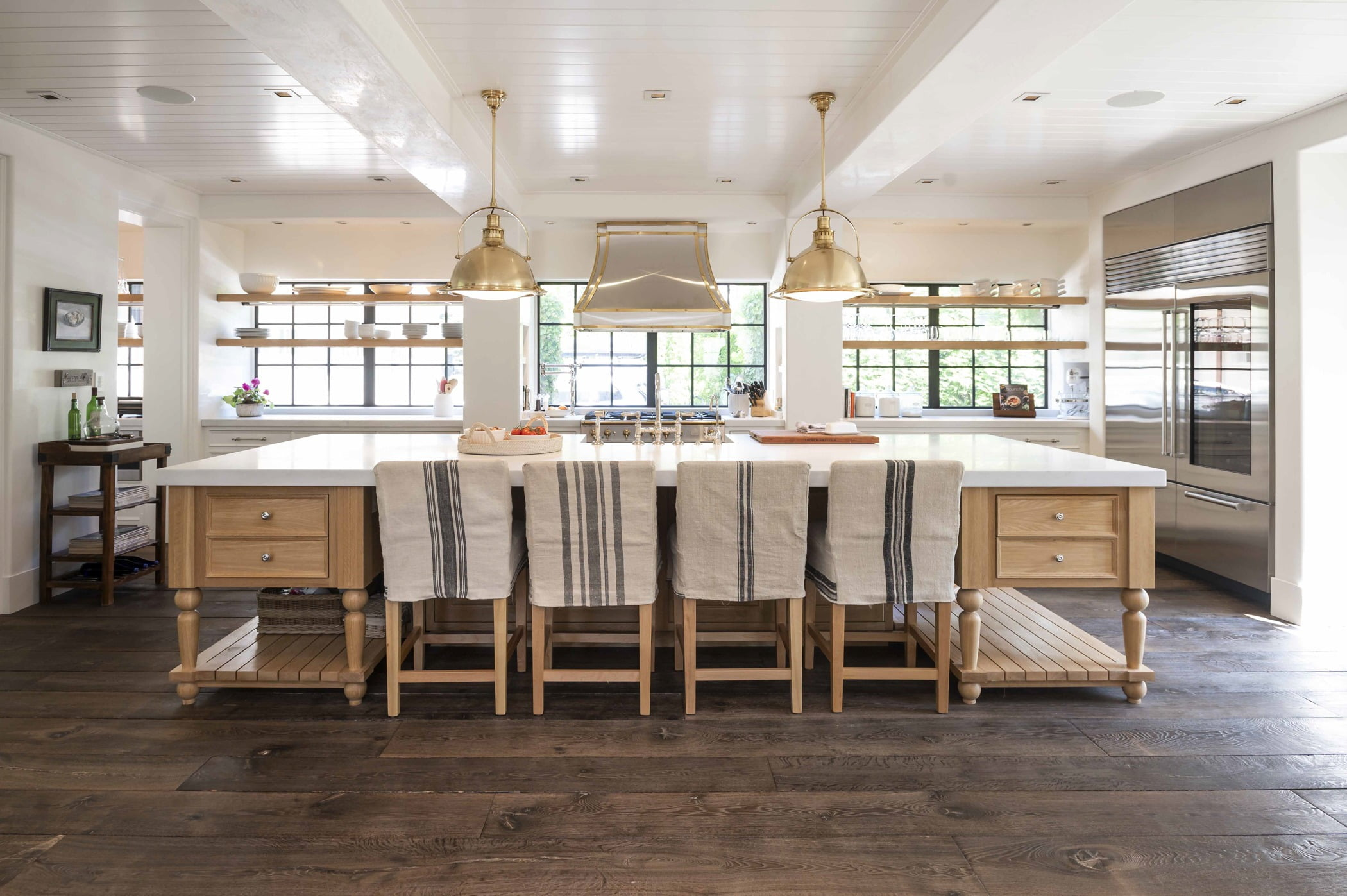 Transitional kitchen island with light wood cabinetry, white marble countertops and dark hardwood flooring