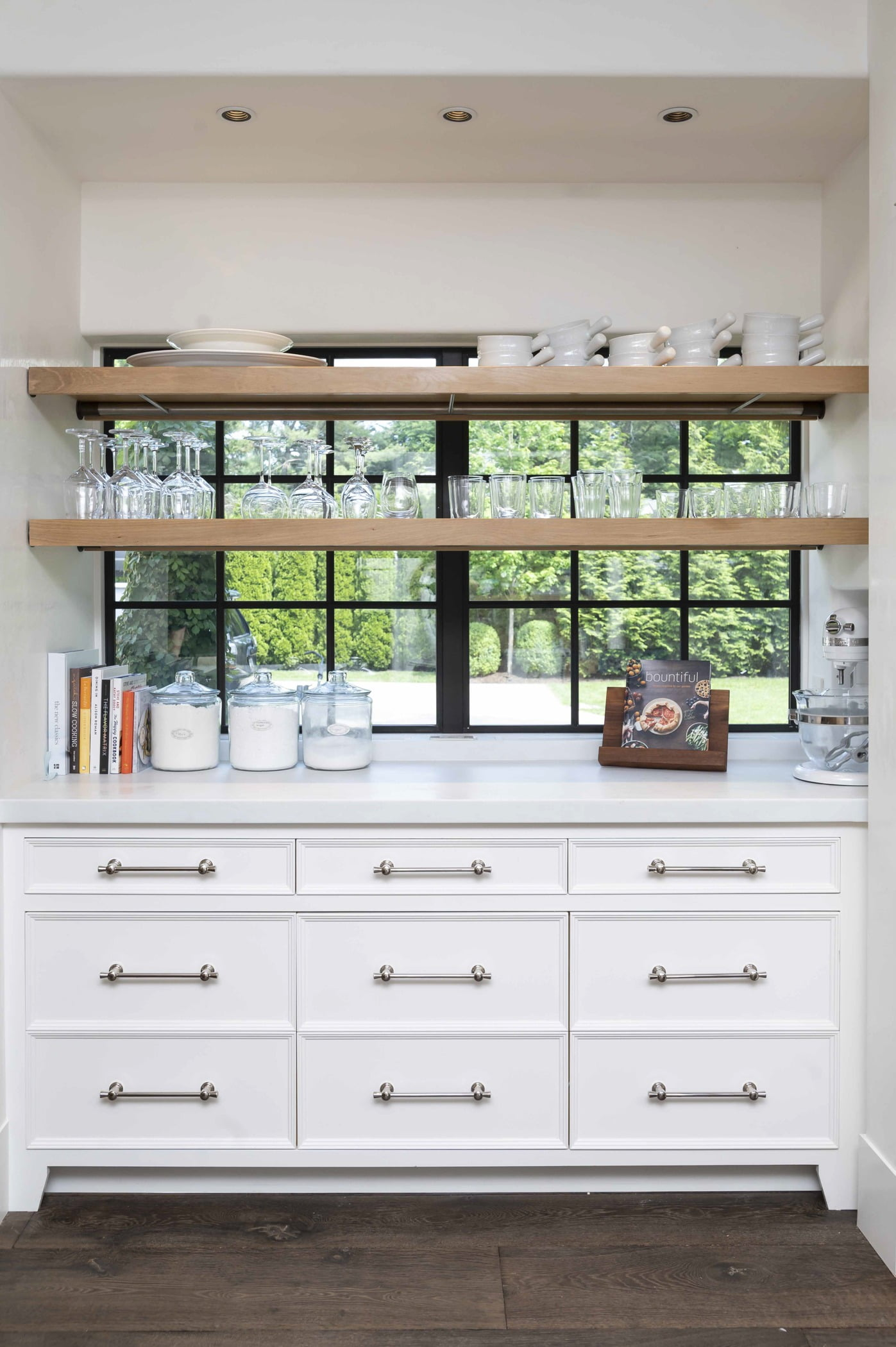 Custom white cabinetry with marble countertops and dark hardwood flooring and wood shelving and black window frames
