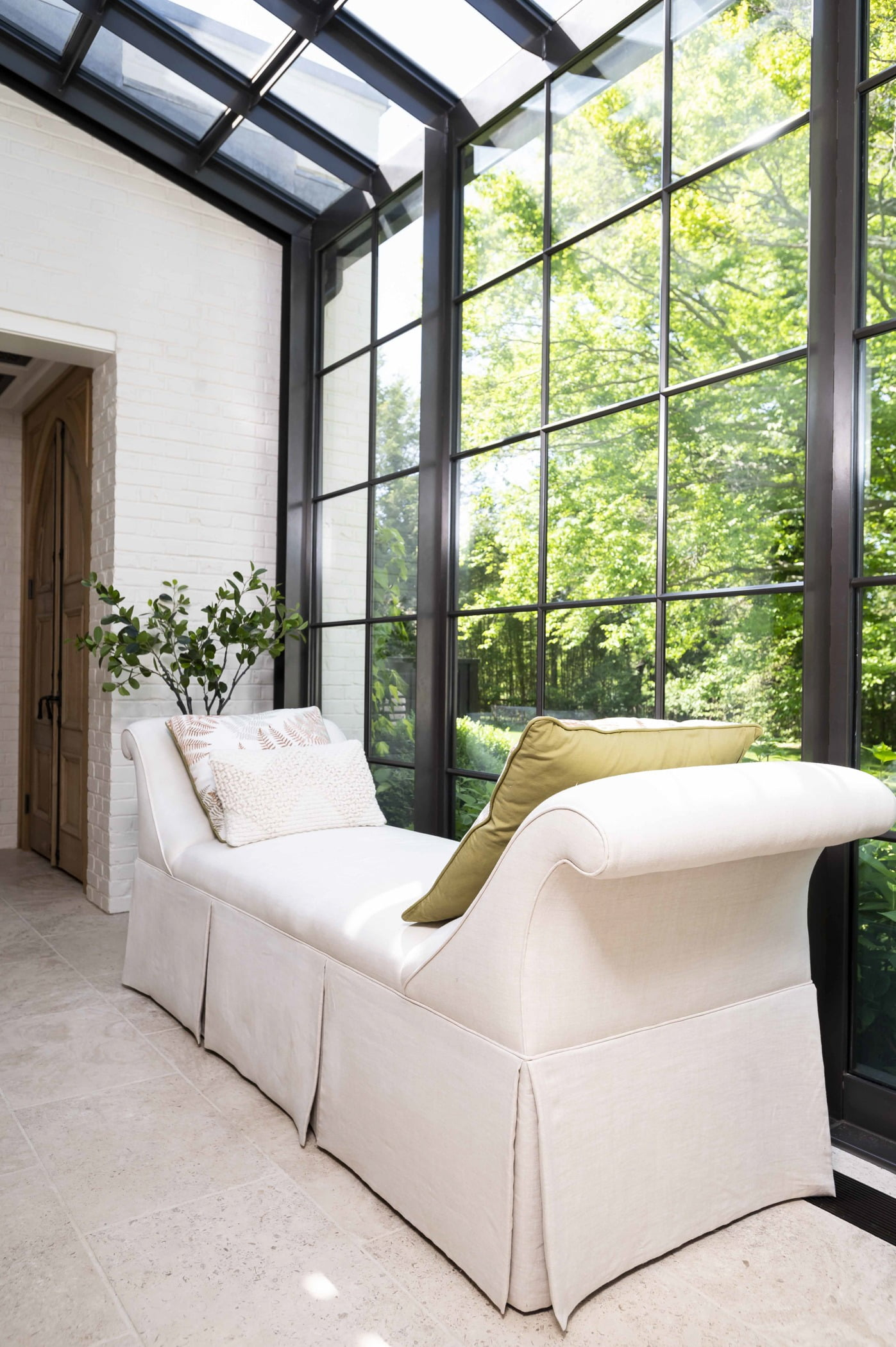 White cushioned lounge chair/bench beside black metal window frames