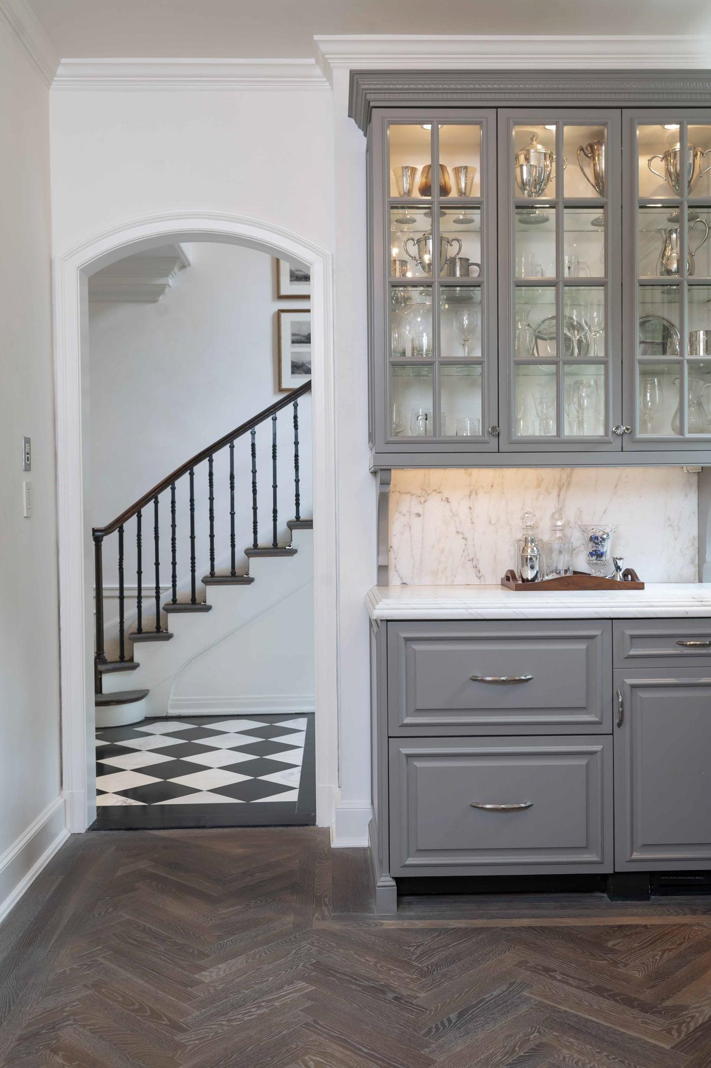 Traditional kitchen area with custom light grey cabinetry, marble countertops, and dark chevron hardwood flooring (Doorway view)
