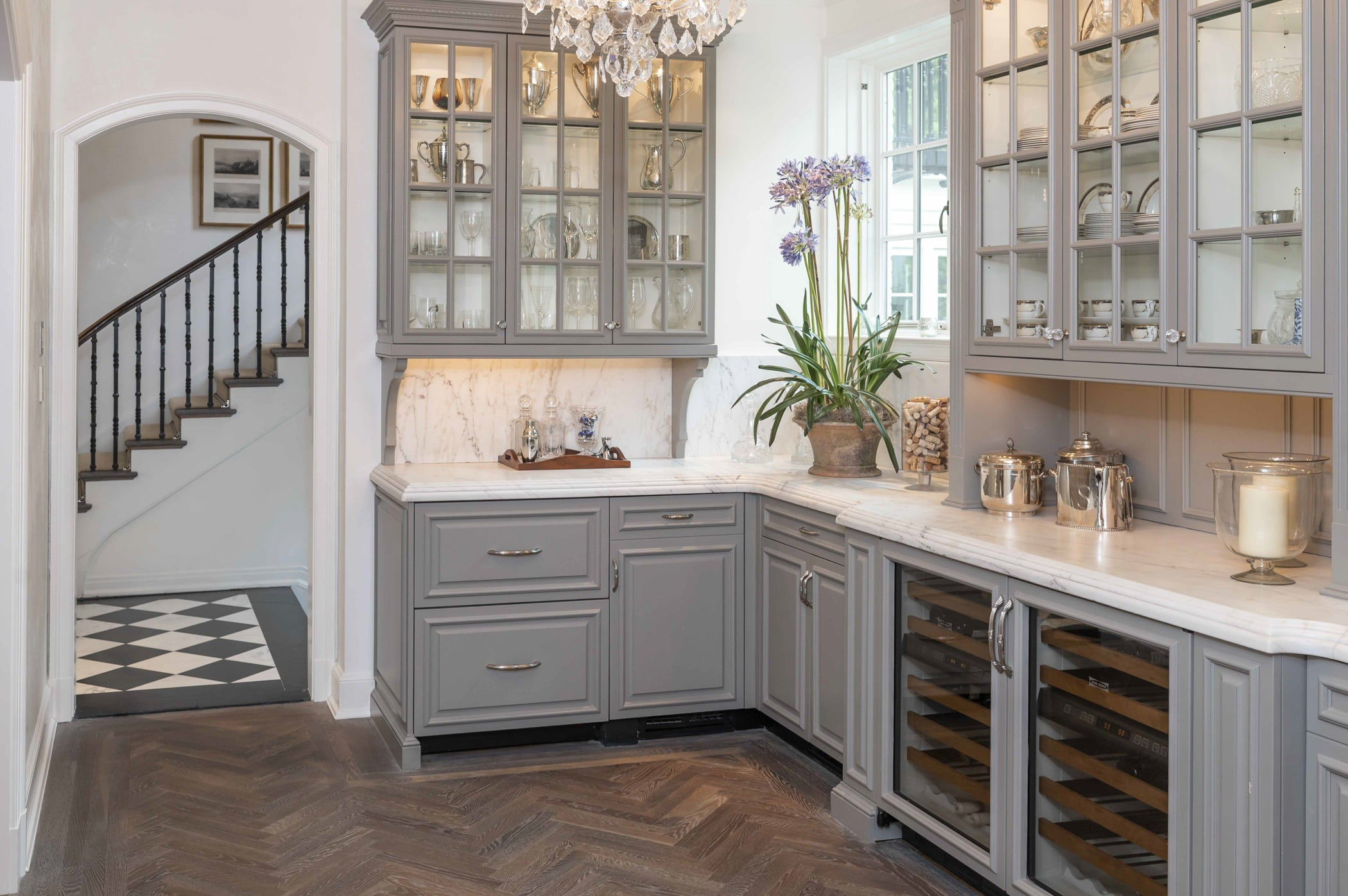 Traditional kitchen area with custom light grey cabinetry, marble countertops, ornate crystal chandelier, and dark chevron hardwood flooring (Doorway view)