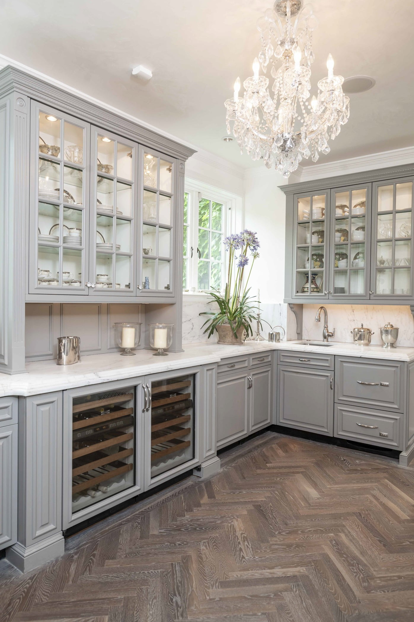 Traditional kitchen area with custom light grey cabinetry, marble countertops, ornate crystal chandelier, and dark chevron hardwood flooring (Different view)