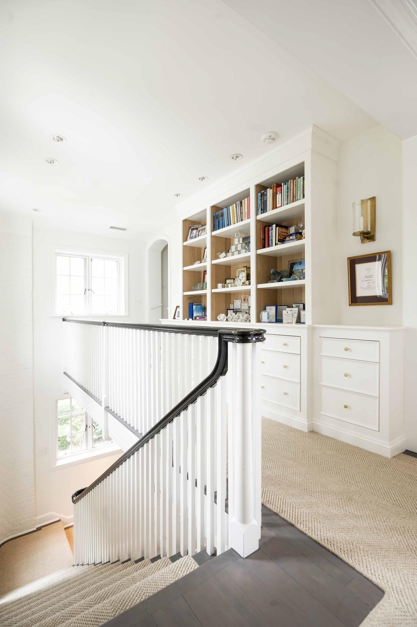 Transitional upstairs hallway, dark hardwood flooring with beige carpet, black and white wood railings