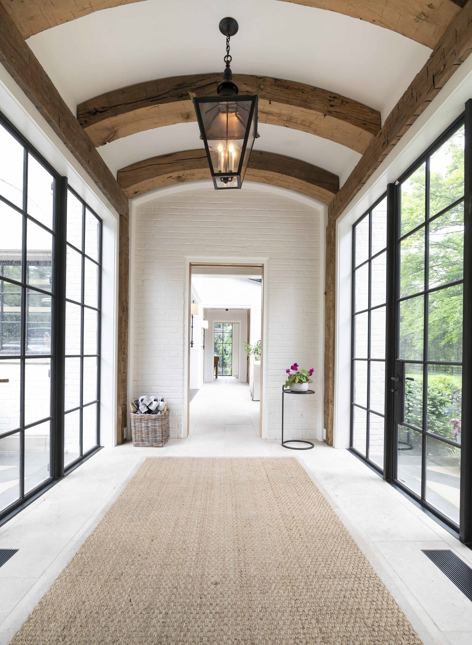 Contemporary/modern hallway with thick wooden ceiling arches, white tile flooring, and black steel framed doors and windows on either side (3)