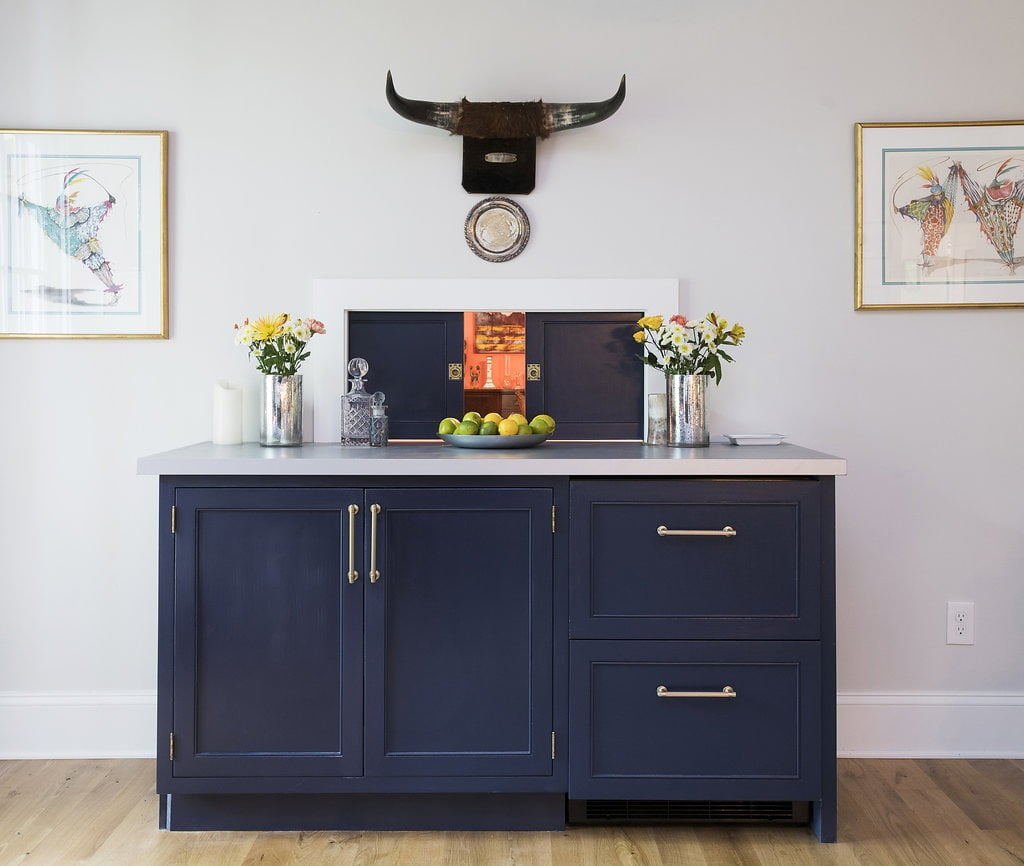 Modern bohemian custom bar cabinetry with navy blue cabinets, white countertops and gold hardware designed by Sunnyfields and DACG.