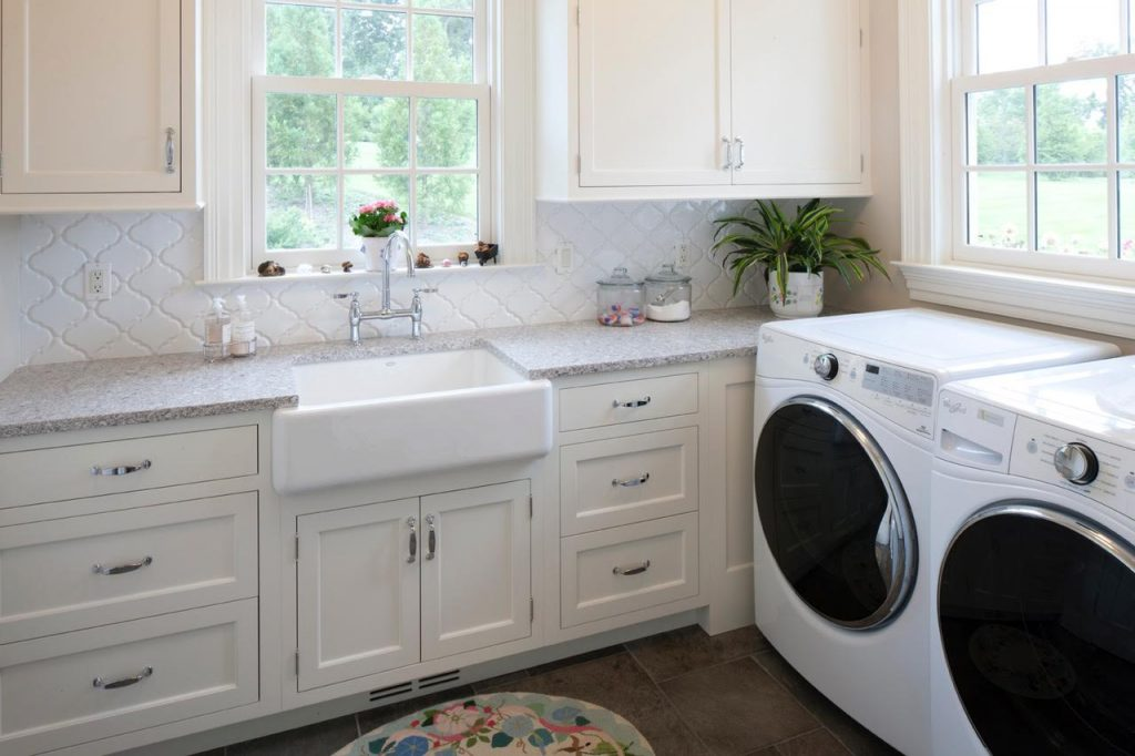 Elegant laundry room with cream cabinets, a farm sink, white tile backsplash and a modern washer and dryer.