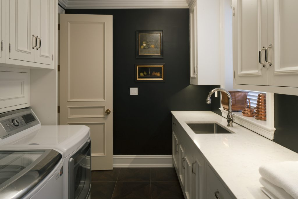 Spacious laundry room with a washer and dryer, and a sink, marble countertops and custom cabinets on the right side.