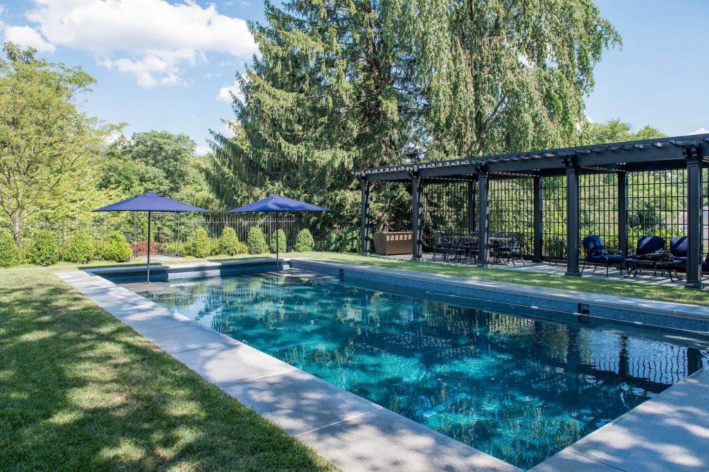 Transitional backyard pool with long dark metal pergola