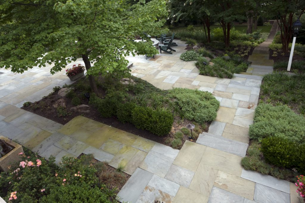 Outdoor garden with tile, seating and a newly planted tree remodeled by DACG.
