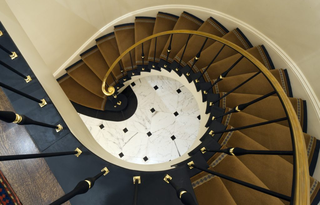 Victorian style metal spiral staircase with gold trim, gold carpet, and granite tile flooring