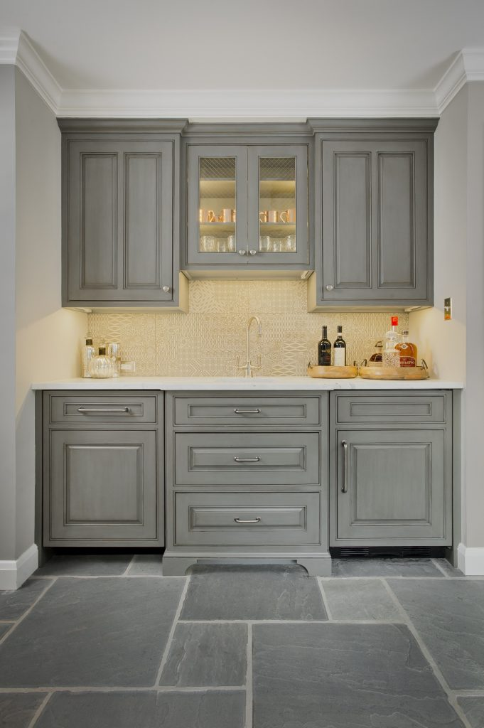Transitional kitchenette with light grey custom cabinetry, grey stone tile flooring, marble countertop, and textured backsplash