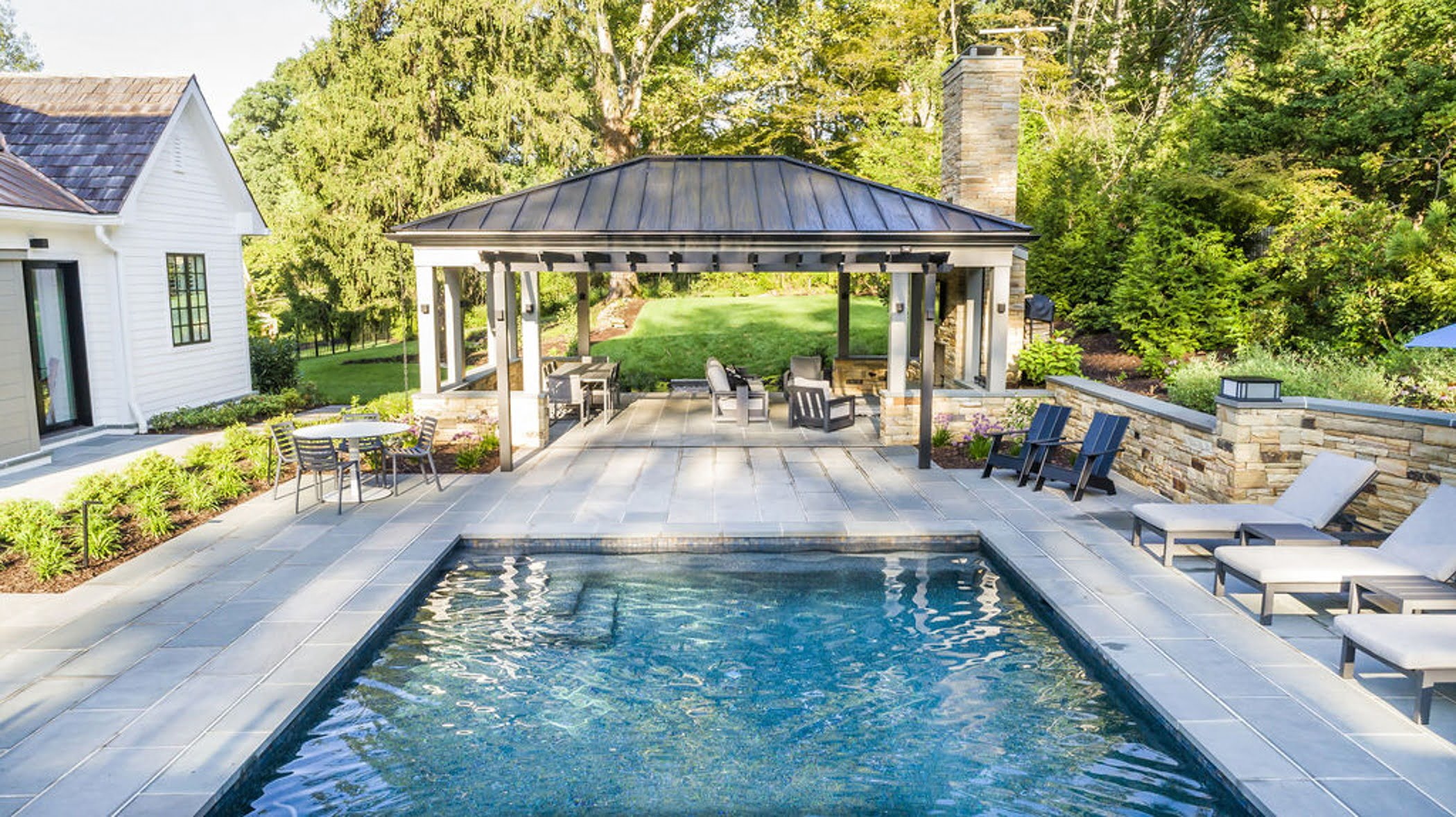 Transitional backyard patio bar and pool house with concrete pavers and cobblestone accented retaining walls (Different view)