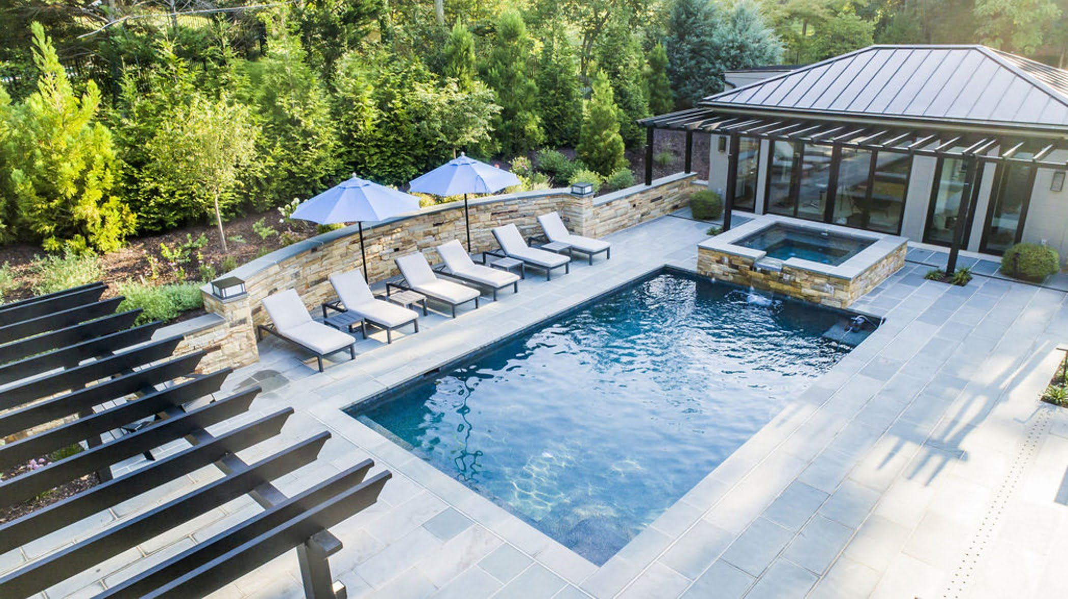 Transitional backyard patio bar and pool house with concrete pavers and cobblestone accented retaining walls and hot tub (Aerial)