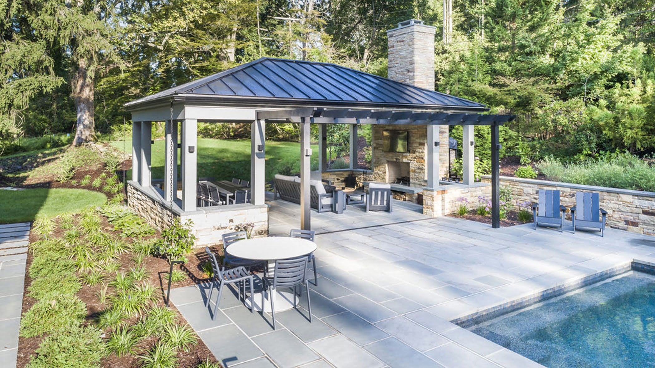 Transitional backyard patio bar and pergola with concrete pavers and cobblestone accented retaining walls