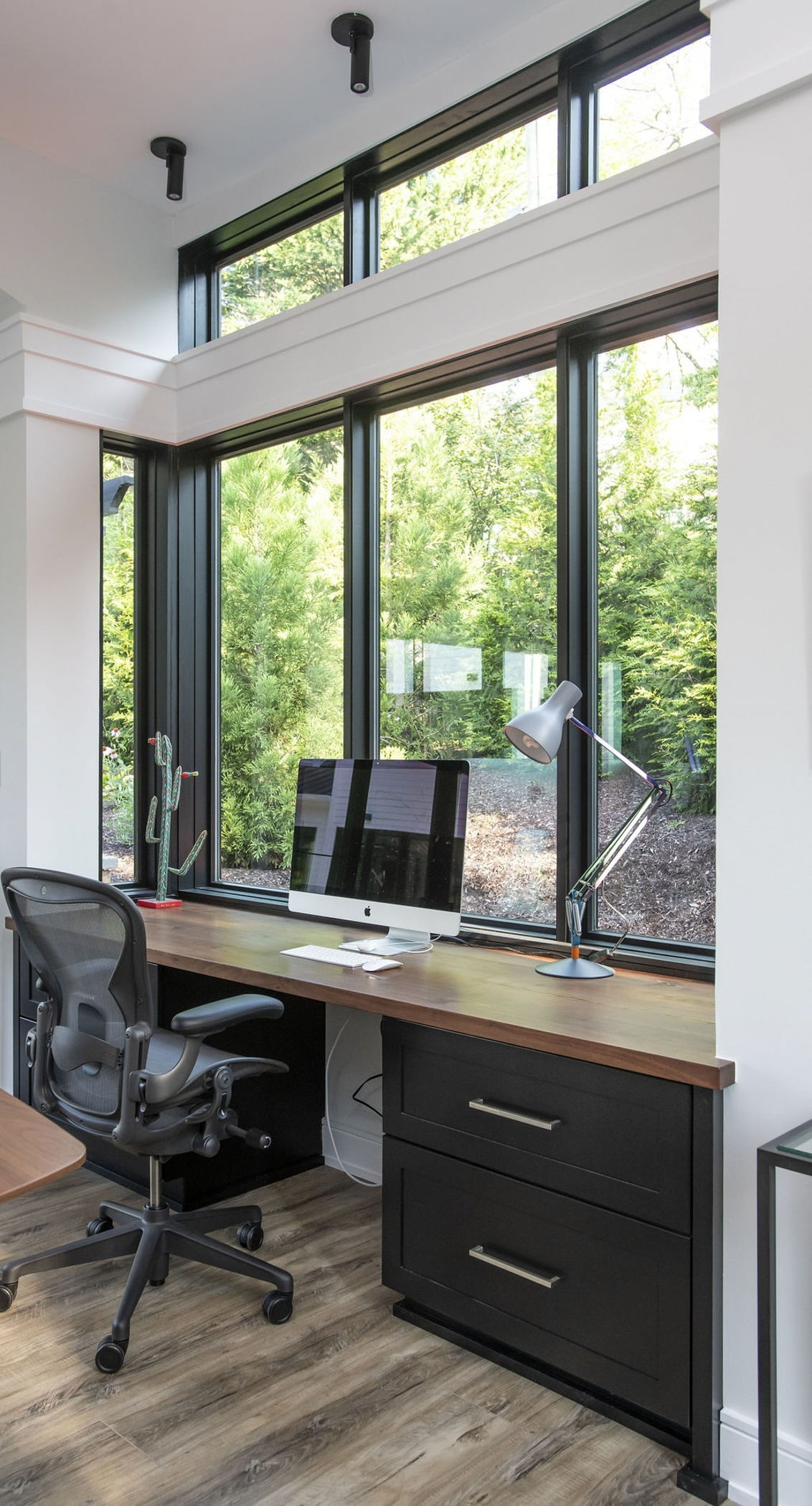 Modern office desk space with light hardwood flooring, black cabinetry, wood countertops and ceiling-high windows