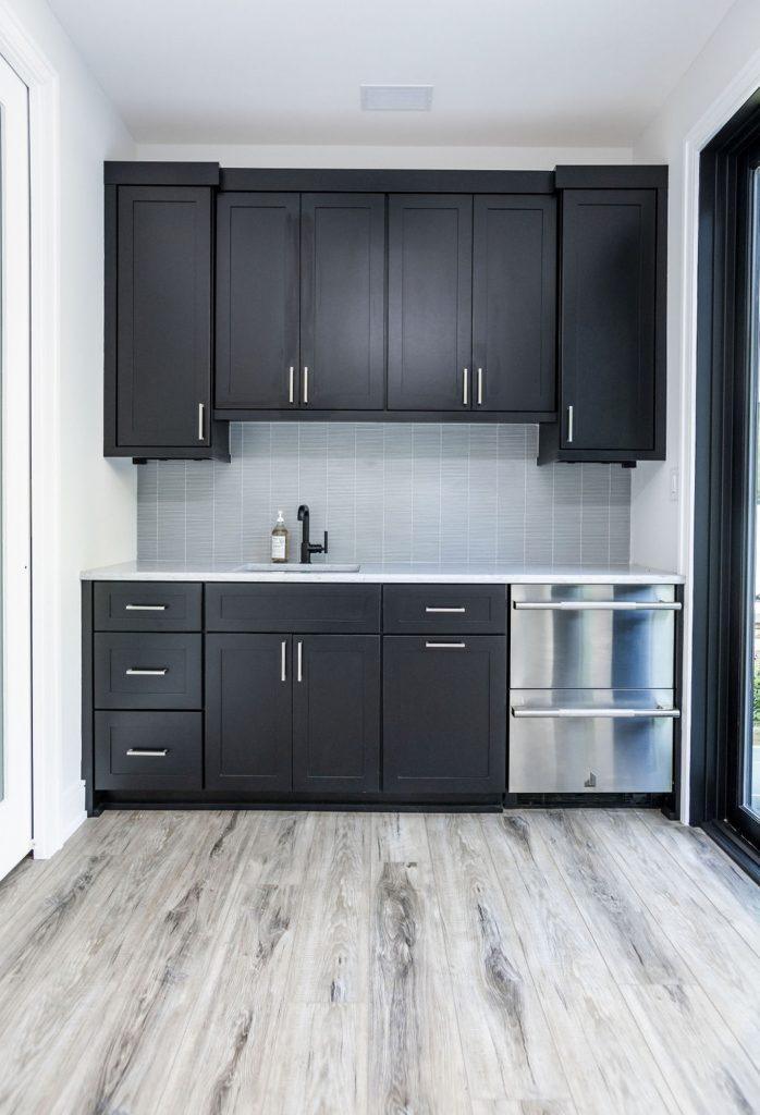 Transitional/Modern kitchenette with dark wood cabinetry, light grey tile backsplash, and light hardwood flooring