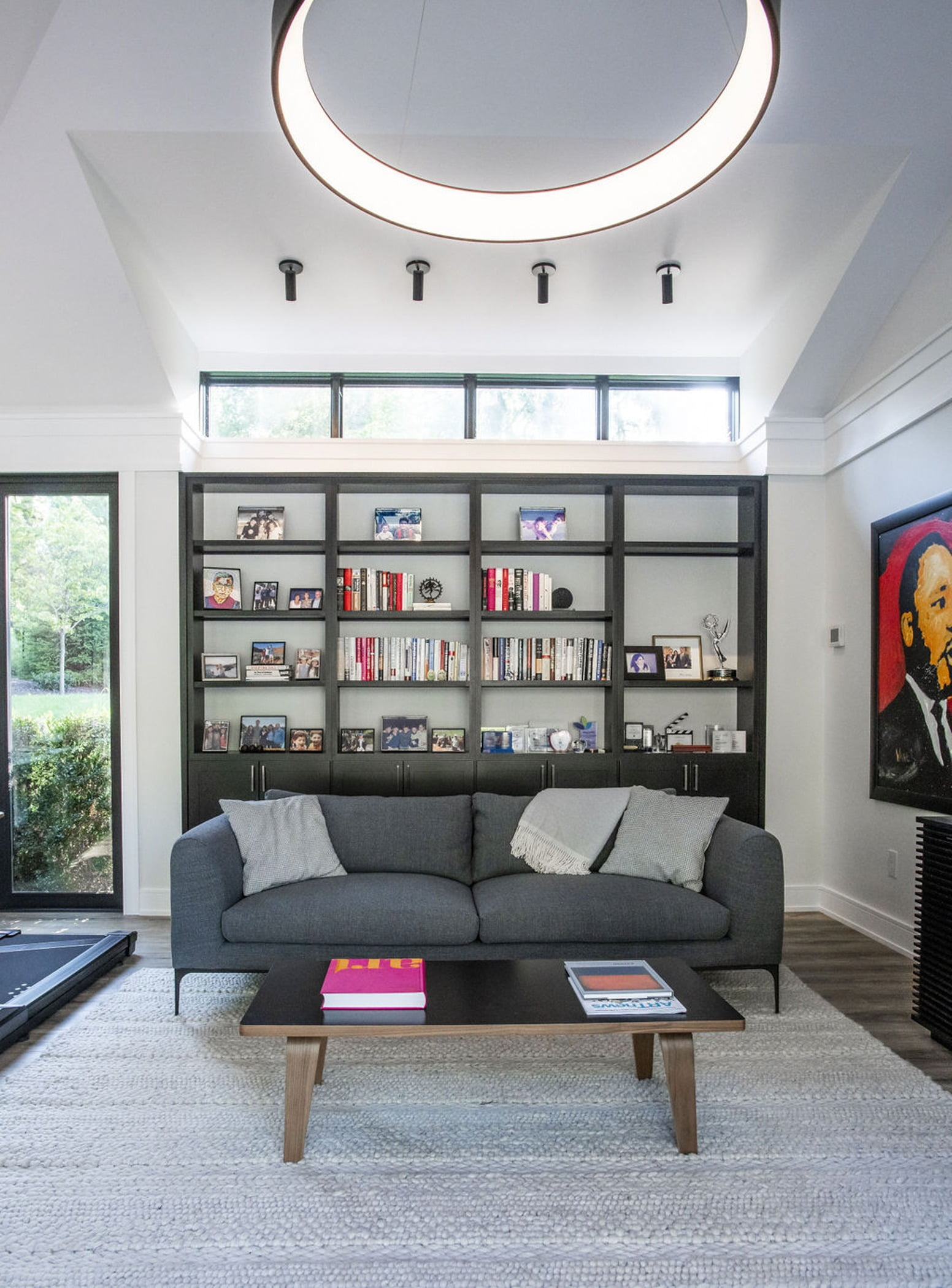 Modern office space with floor to ceiling windows, built in wall shelves and minimalistic furniture (Couch view)
