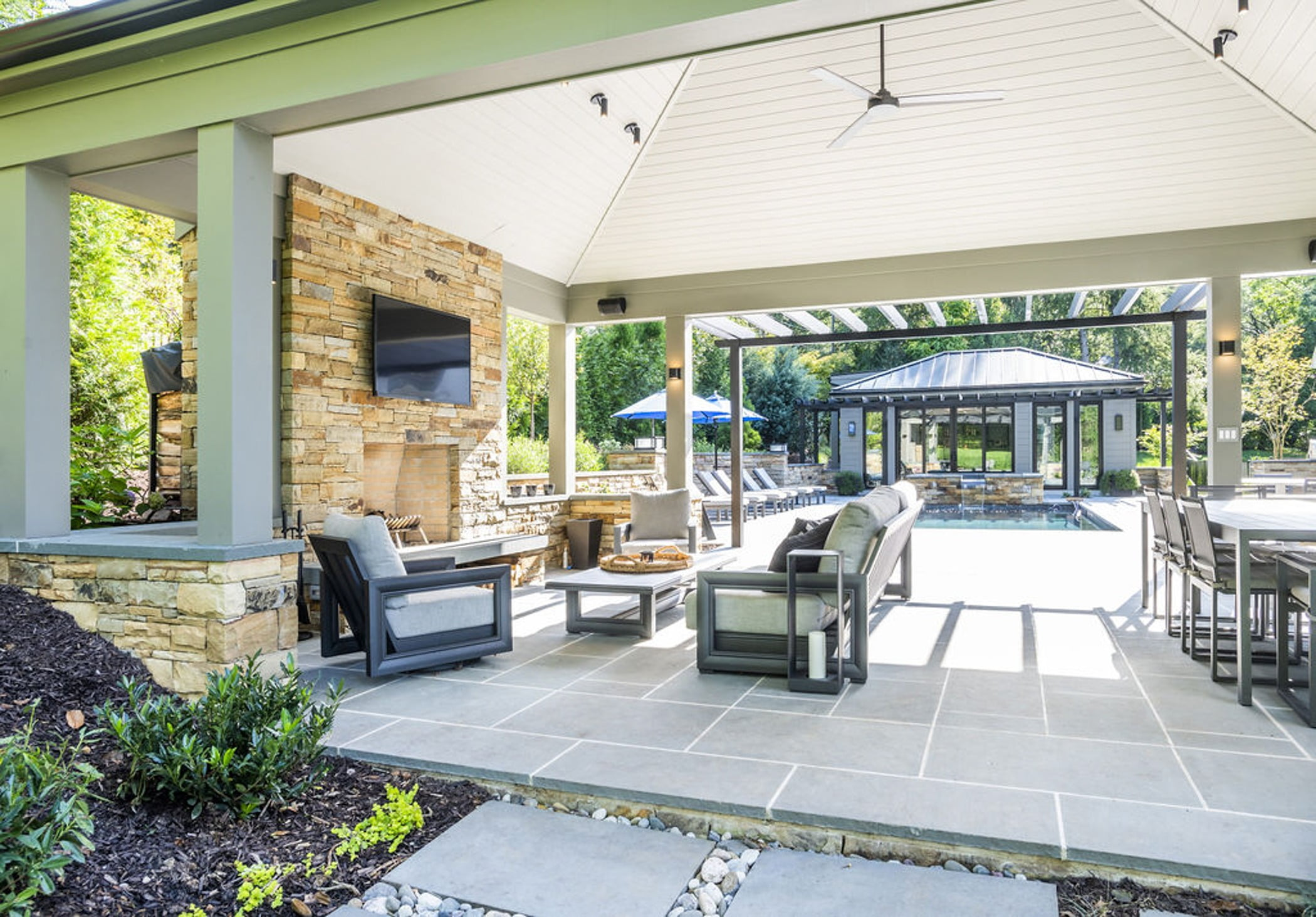 Transitional backyard patio bar and poolhouse with concrete pavers and cobblestone accented retaining walls and hot tub