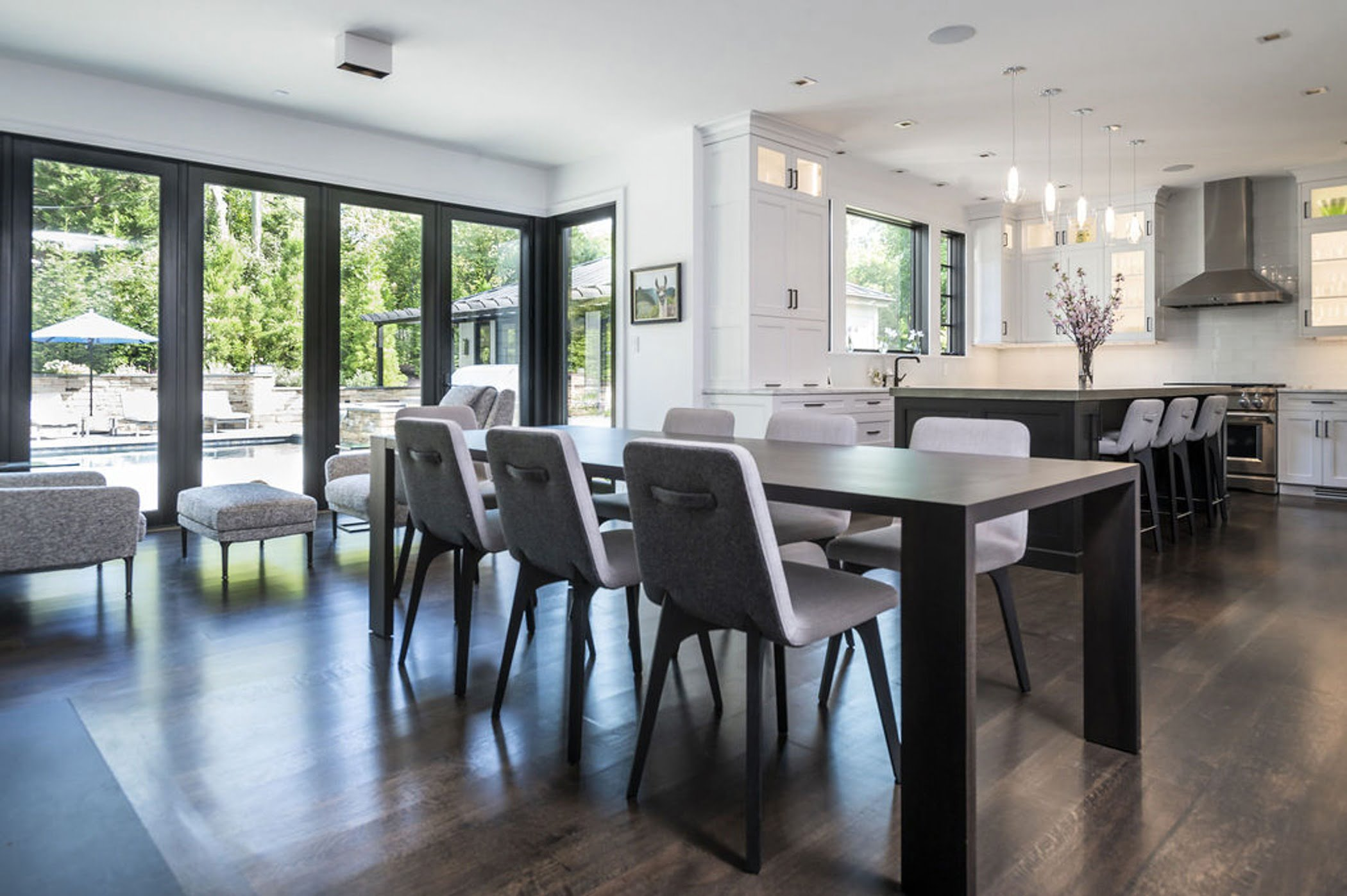 Modern dining area with sleek dark hardwood table and flooring, and matching dining chairs