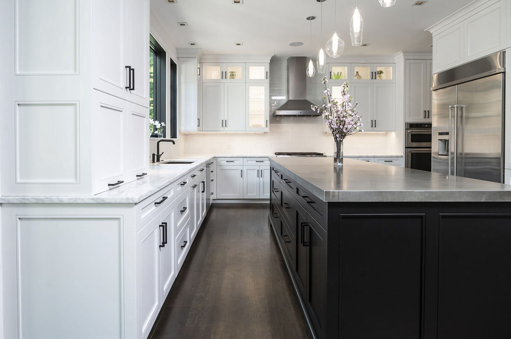 Modern kitchen remodel with an open concept layout including white cabinetry, marble countertop and a dark wood center island (Different view)