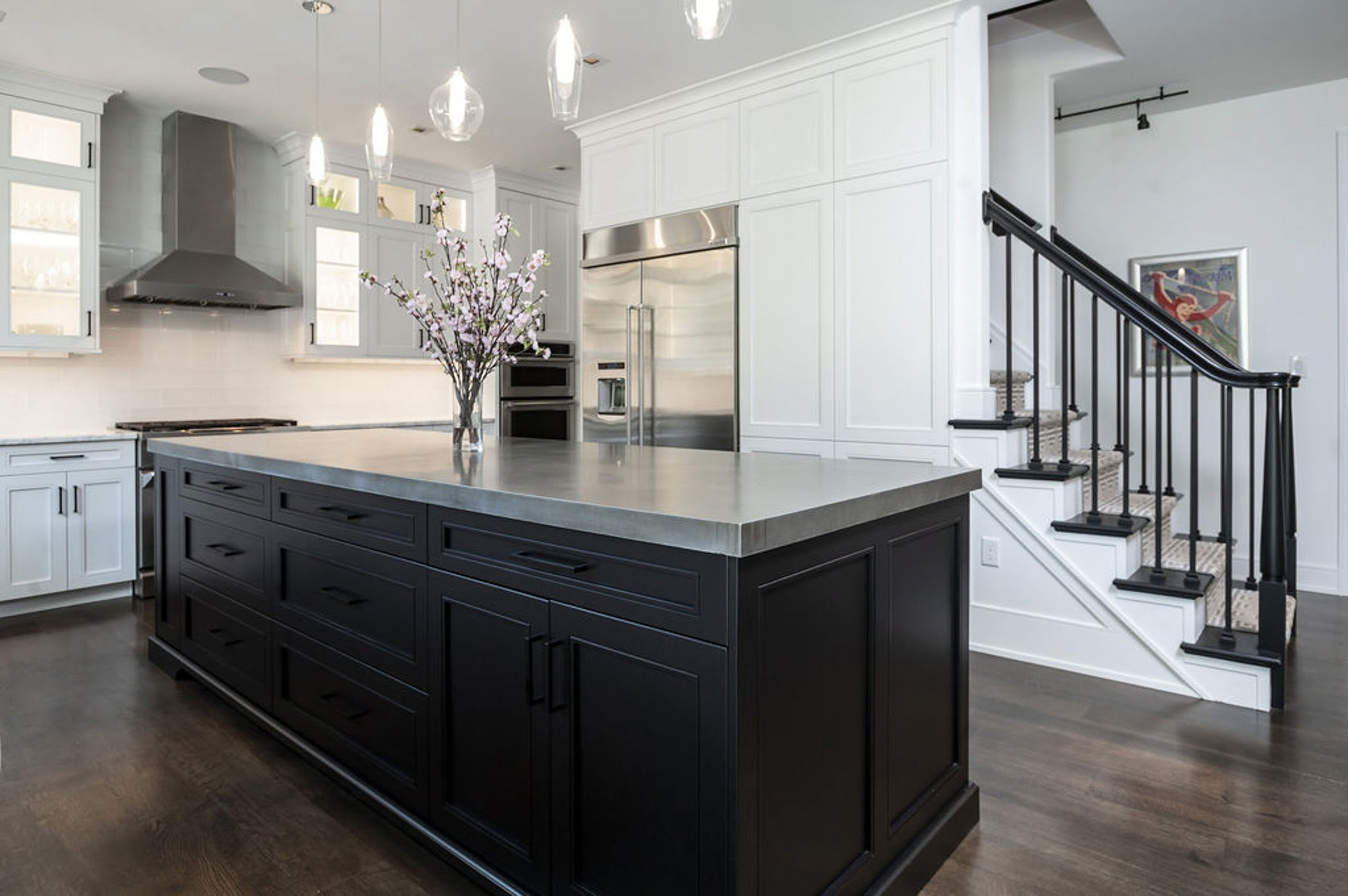 Modern kitchen remodel with an open concept layout including white cabinetry, marble countertop and a dark wood center island (2)