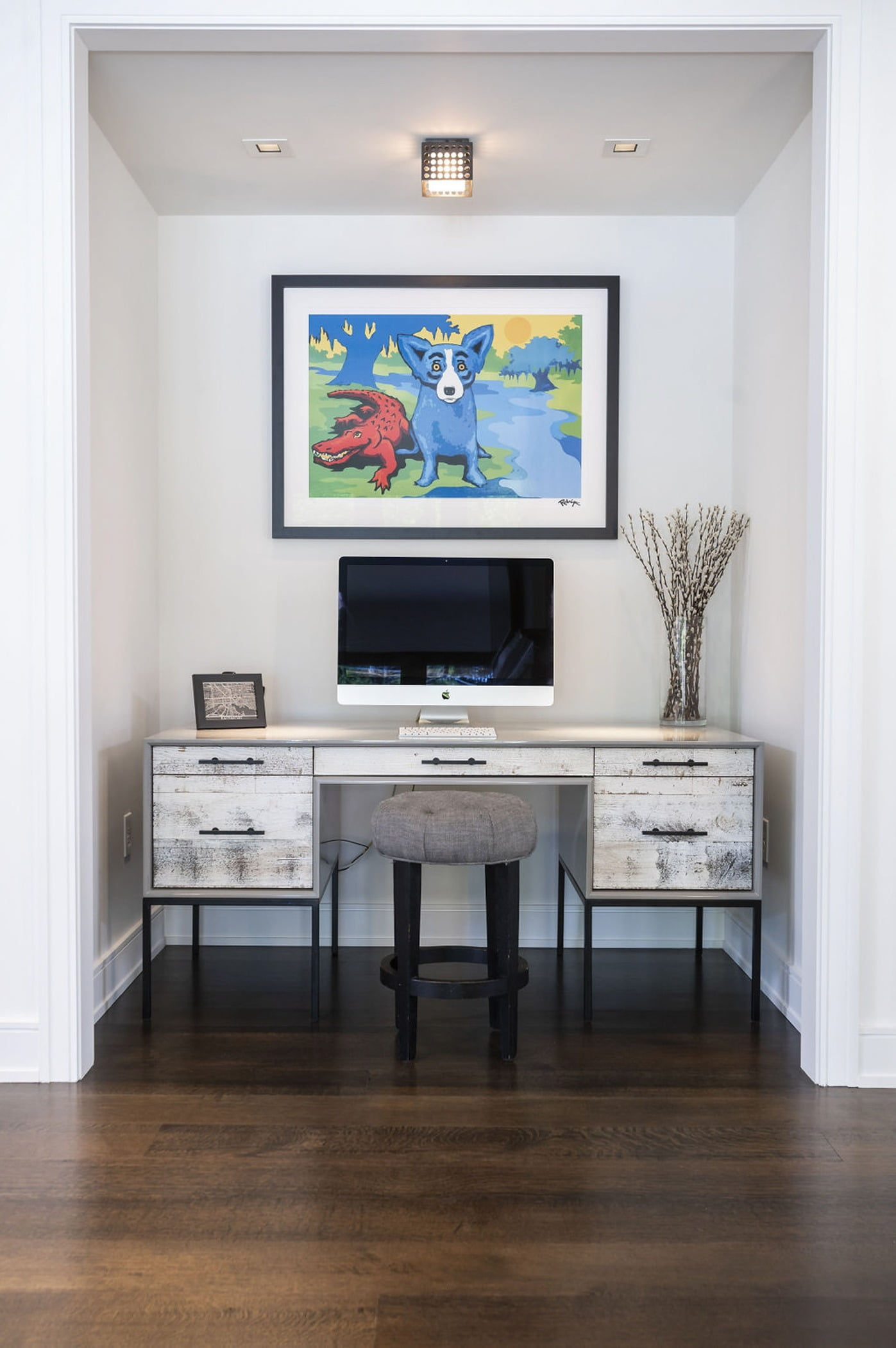 Contemporary desk with unstained wood cabinetry, wooden pouf stool, and dark hardwood flooring