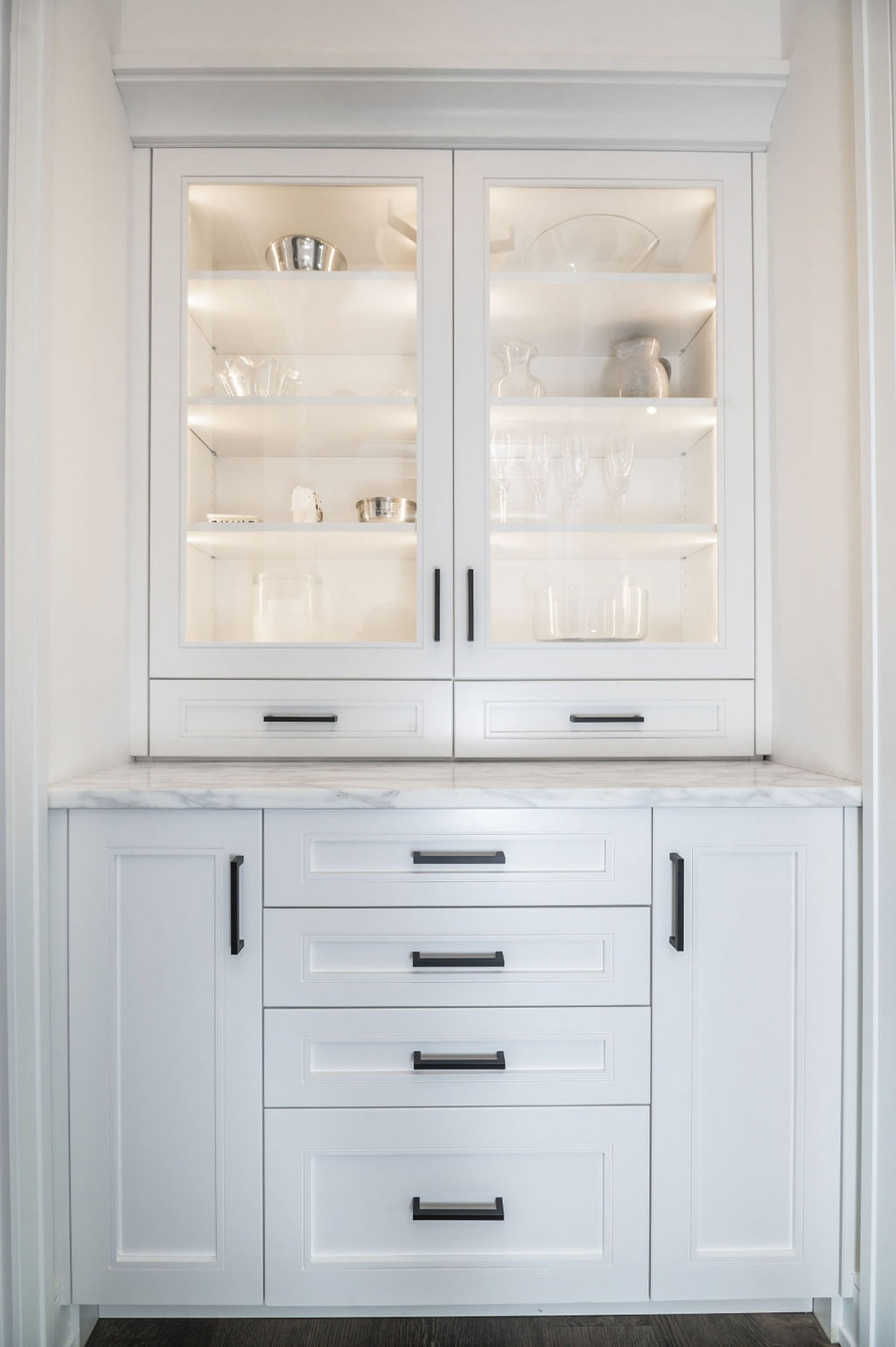 Transitional dining pantry counter with custom white cabinetry and marble countertops