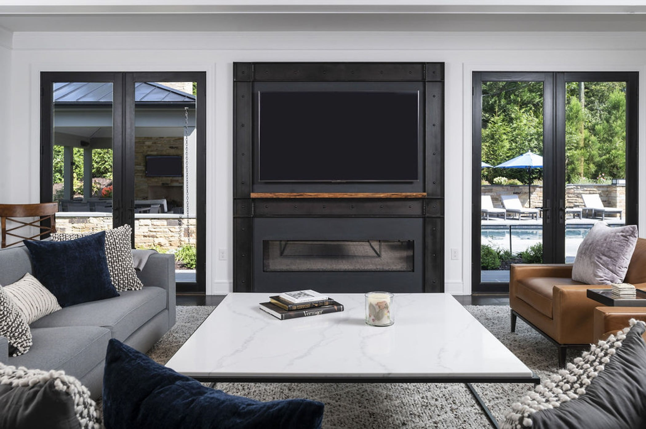 Modern family room with marble coffee table, black steel-framed tv and fireplace, and sleek furniture