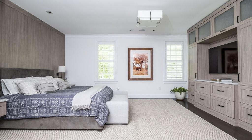 Transitional master bedroom with custom light beige floor-to-ceiling wood cabinetry and bed wall, dark hardwood flooring and white wall color
