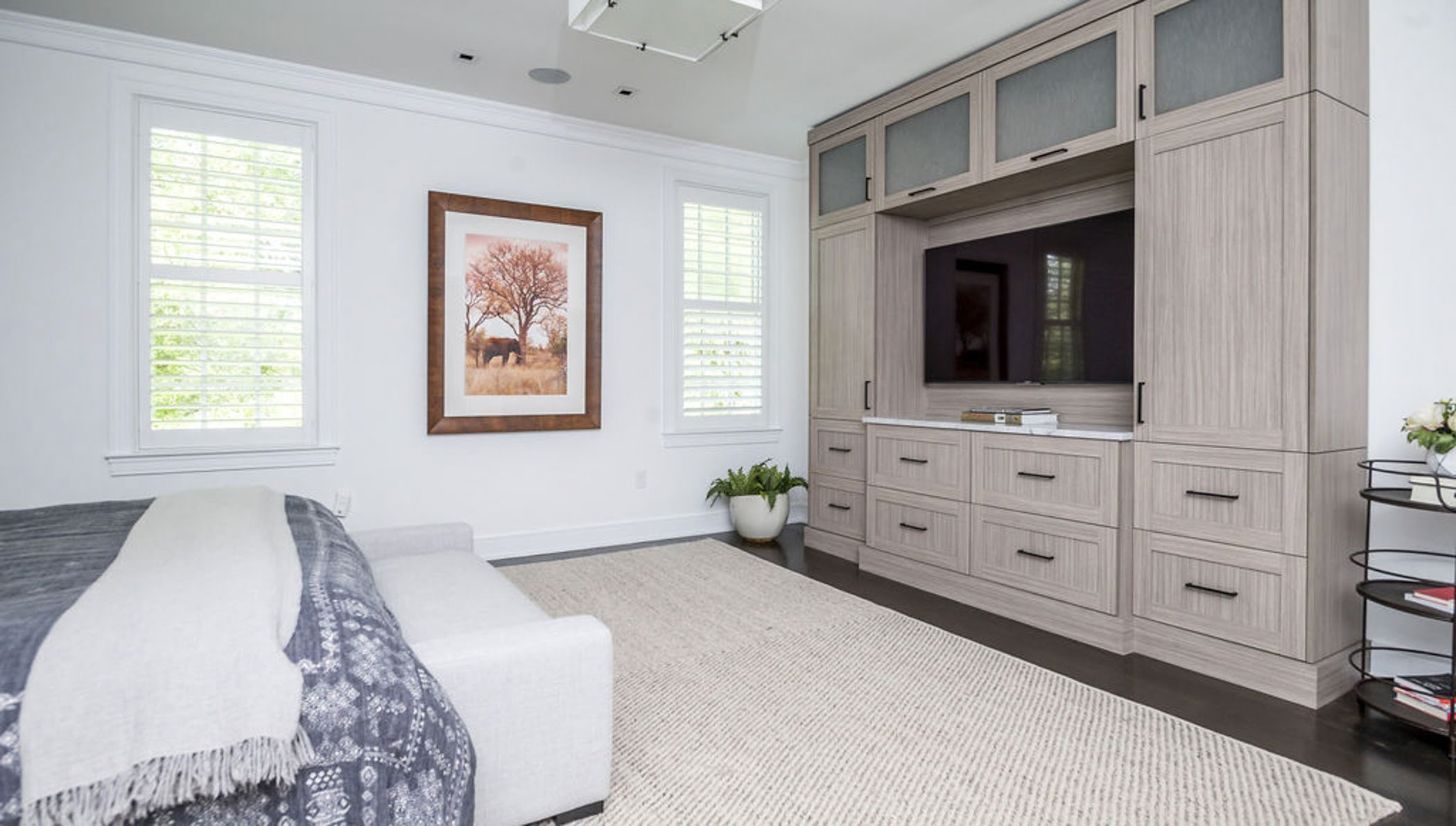 Modern bedroom remodel with a wall-to-wall media console in a light wood color with black drawer pulls.