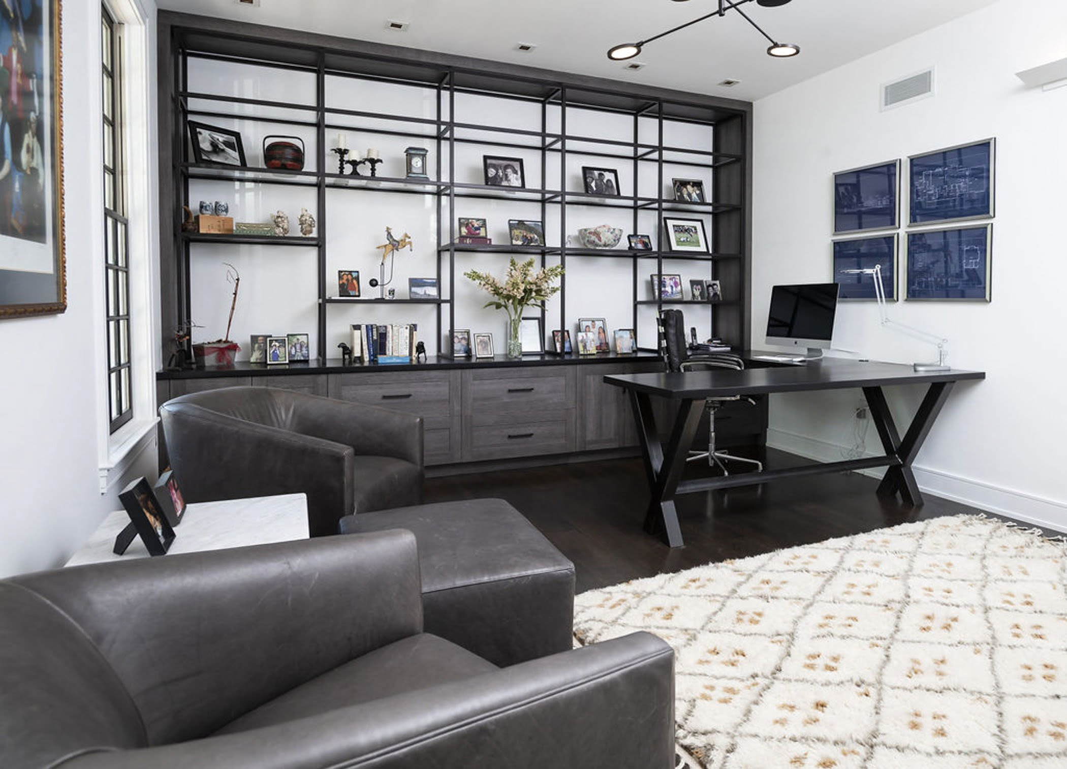 Modern and luxurious office space with dark wood floors, wall to wall shelving and leather furniture