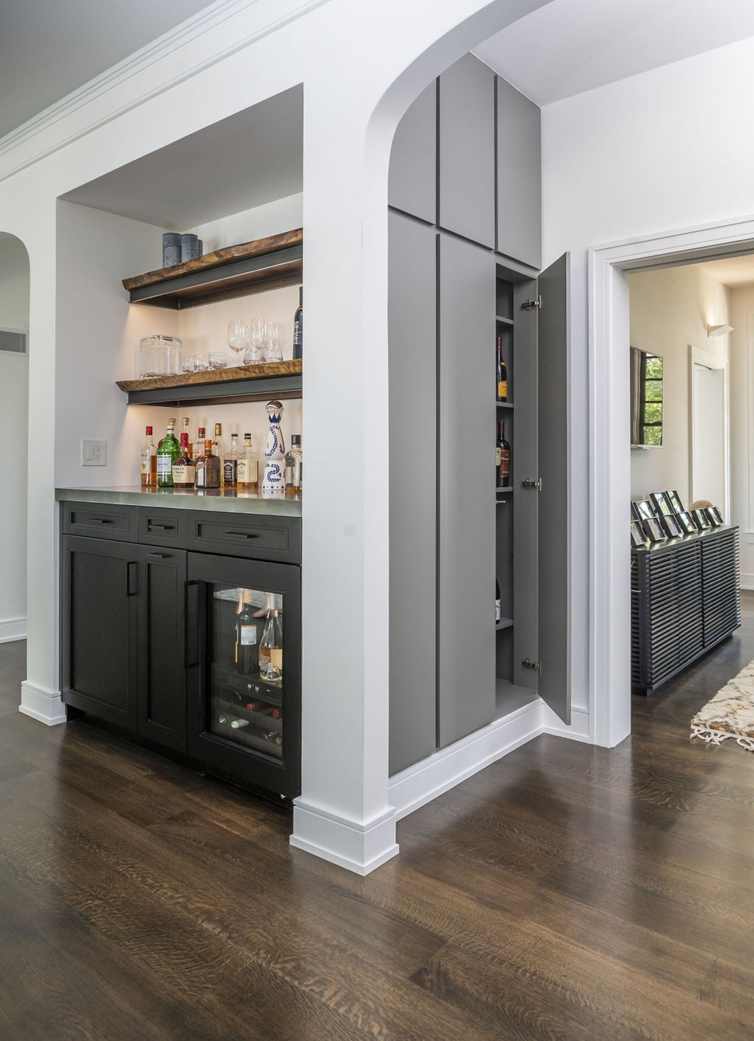 Living room and kitchen space with built in wall cabinetry and a custom, built-in bar