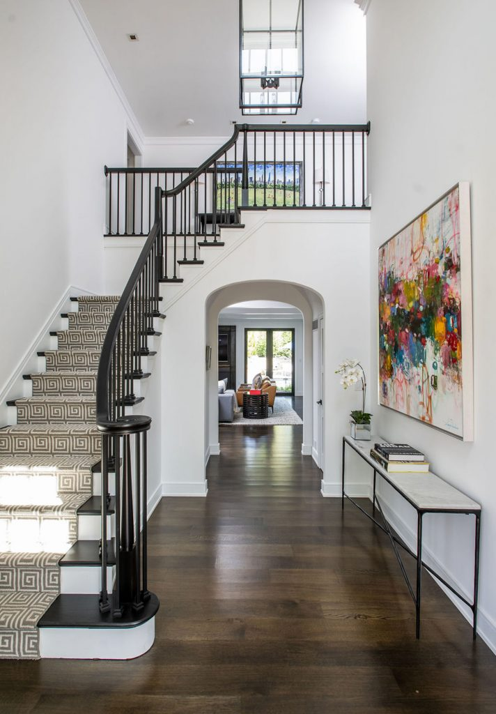 Open-concept entryway with stairs, dark wood floors and arched doorways in a modern home