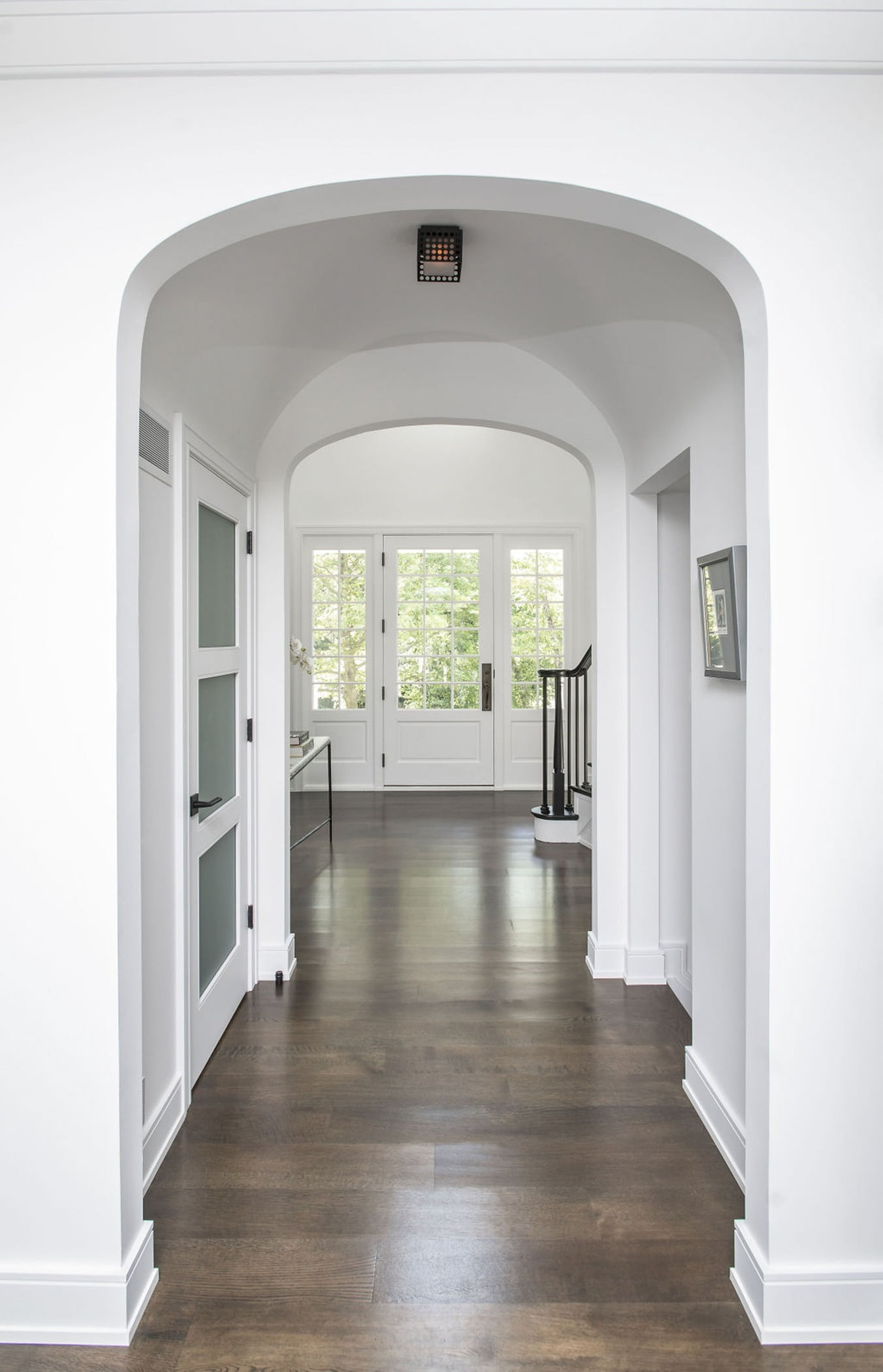 Transitional interior archway with dark hardwood flooring and clean white walls