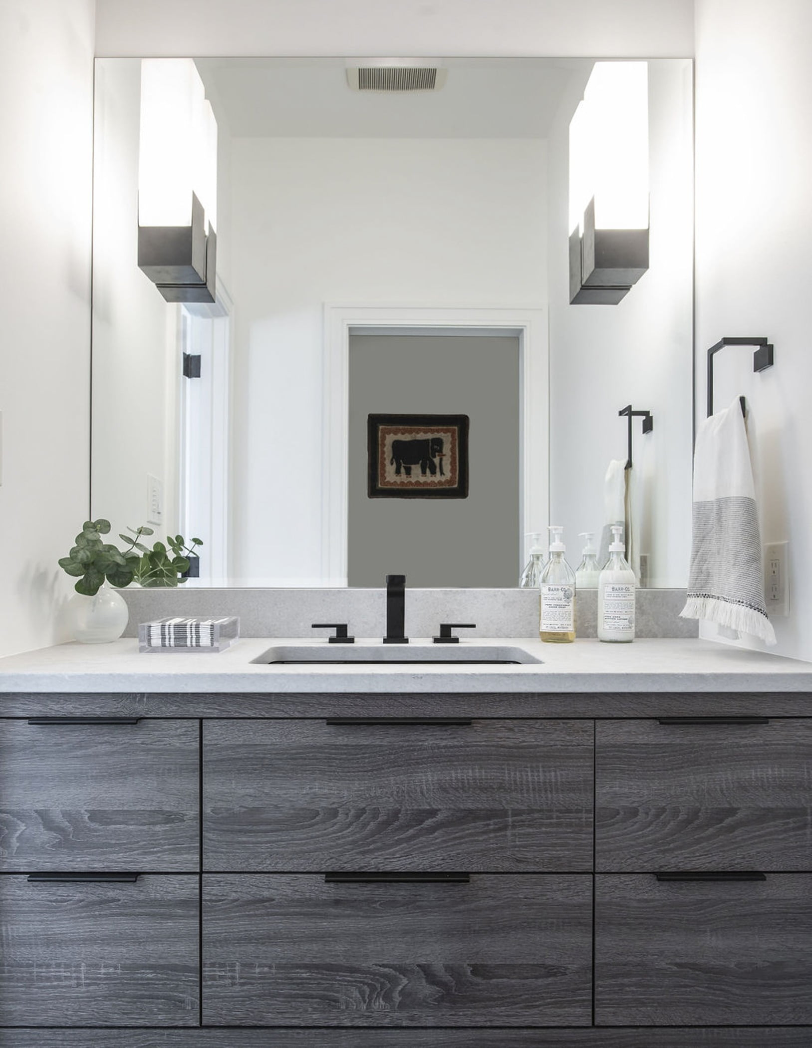 Modern style bathroom sink with dark grey cabinetry, marble countertops, and sleek black handles and faucet